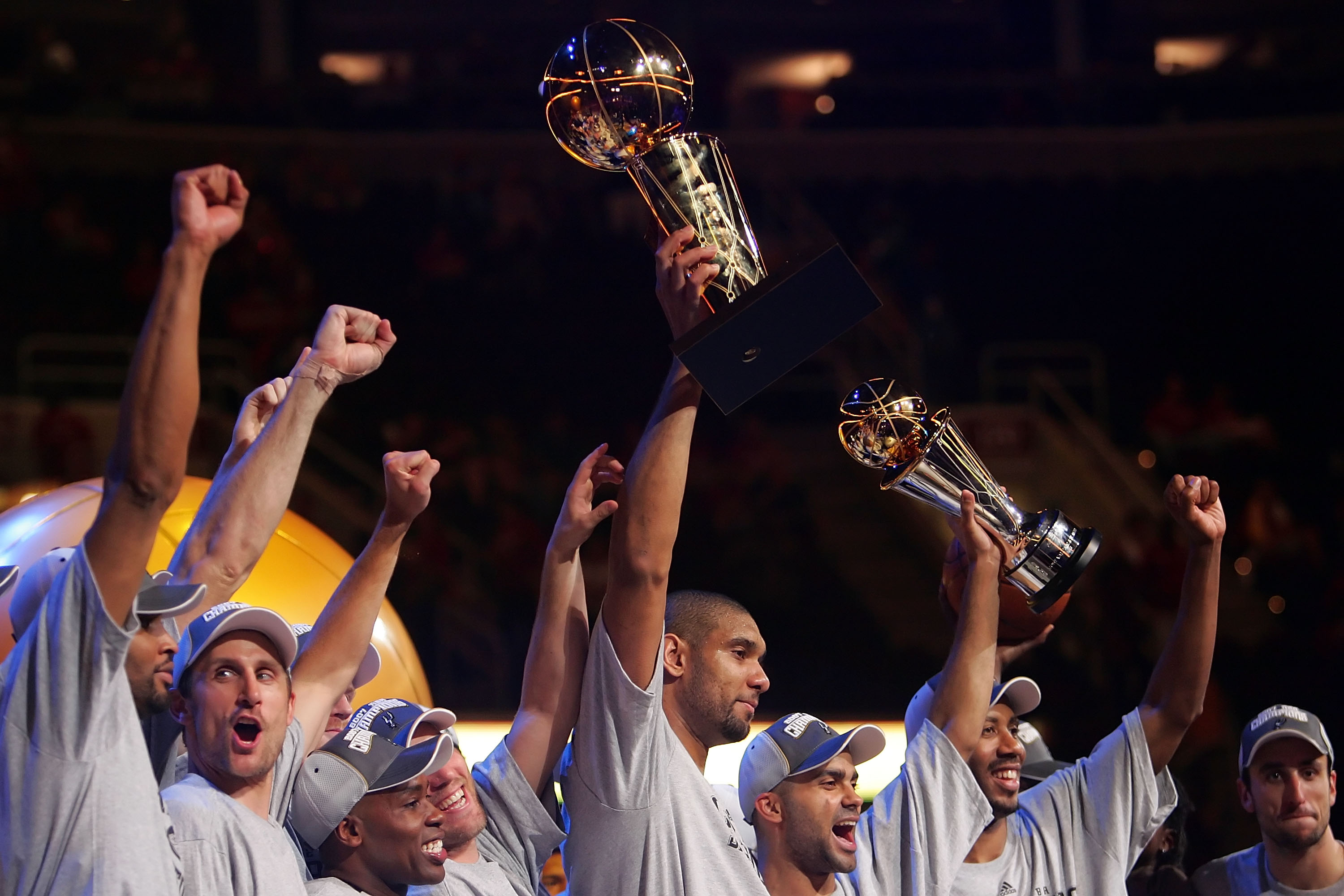 CLEVELAND - JUNE 14:  Members of the San Antonio Spurs celebrate the win as Tim Duncan #21 holds up the Larry O'Brien Championship Trophy and Tony Parker #9 holds up the MVP trophy after winning Game Four of the NBA Finals against the Cleveland Cavaliers