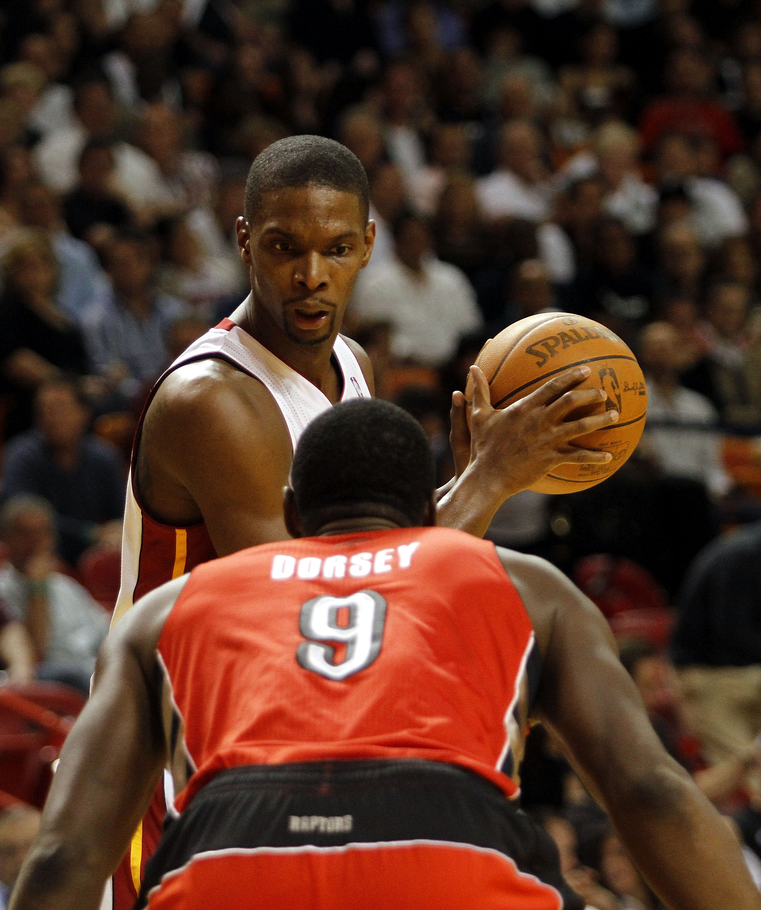 MIAMI - NOVEMBER 13:  Forward Chris Bosh #1 of the Miami Heat against Joey Dorsey #9 of the Toronto Raptors at American Airlines Arena on November 13, 2010 in Miami, Florida. NOTE TO USER: User expressly acknowledges and agrees that, by downloading and or