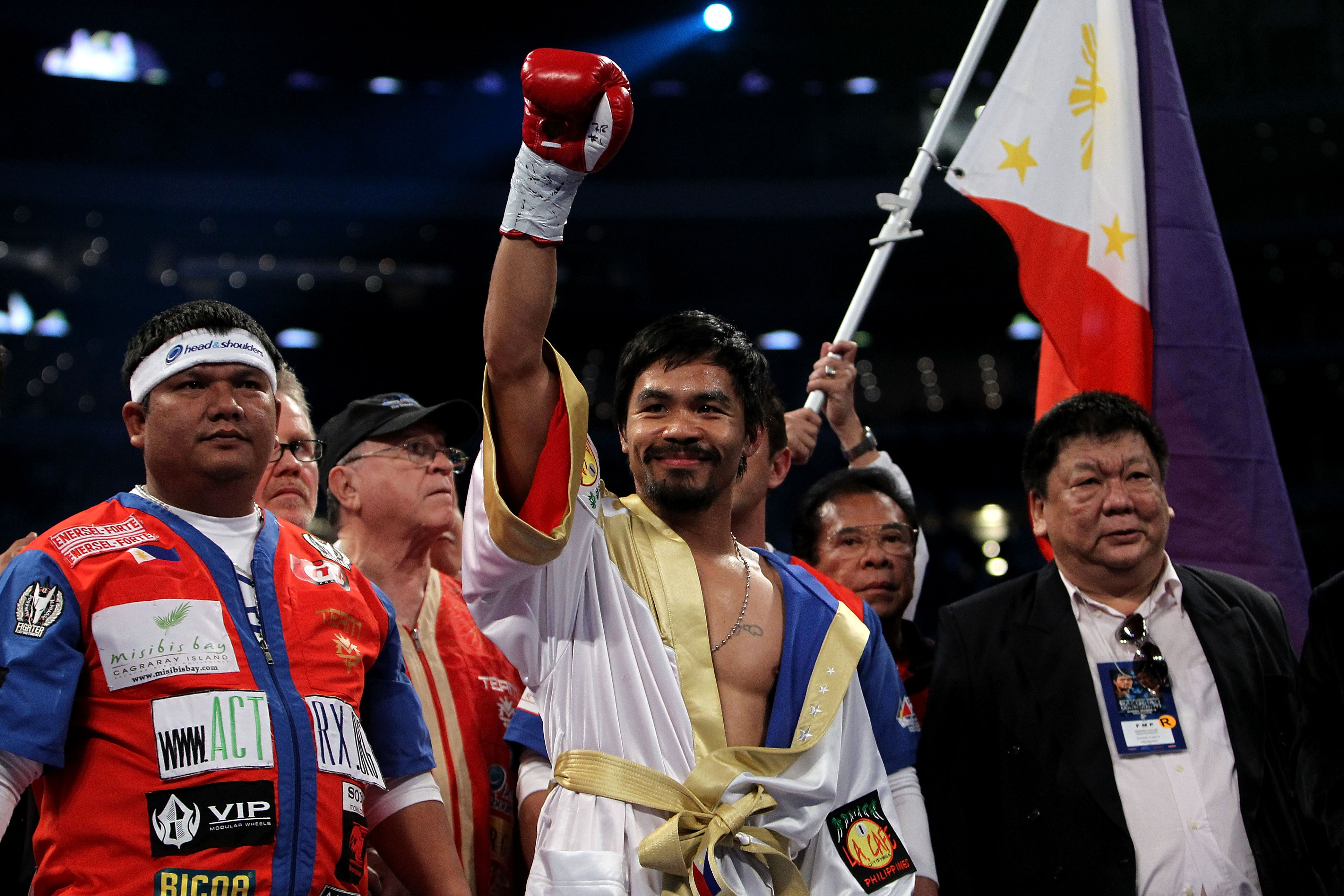 ARLINGTON, TX - NOVEMBER 13:  Manny Pacquiao (white trunks) of the Philippines raises his hand in the air as he stands in the ring waiting to fight against Antonio Margarito (black trunks) of Mexico during their WBC World Super Welterweight Title bout at