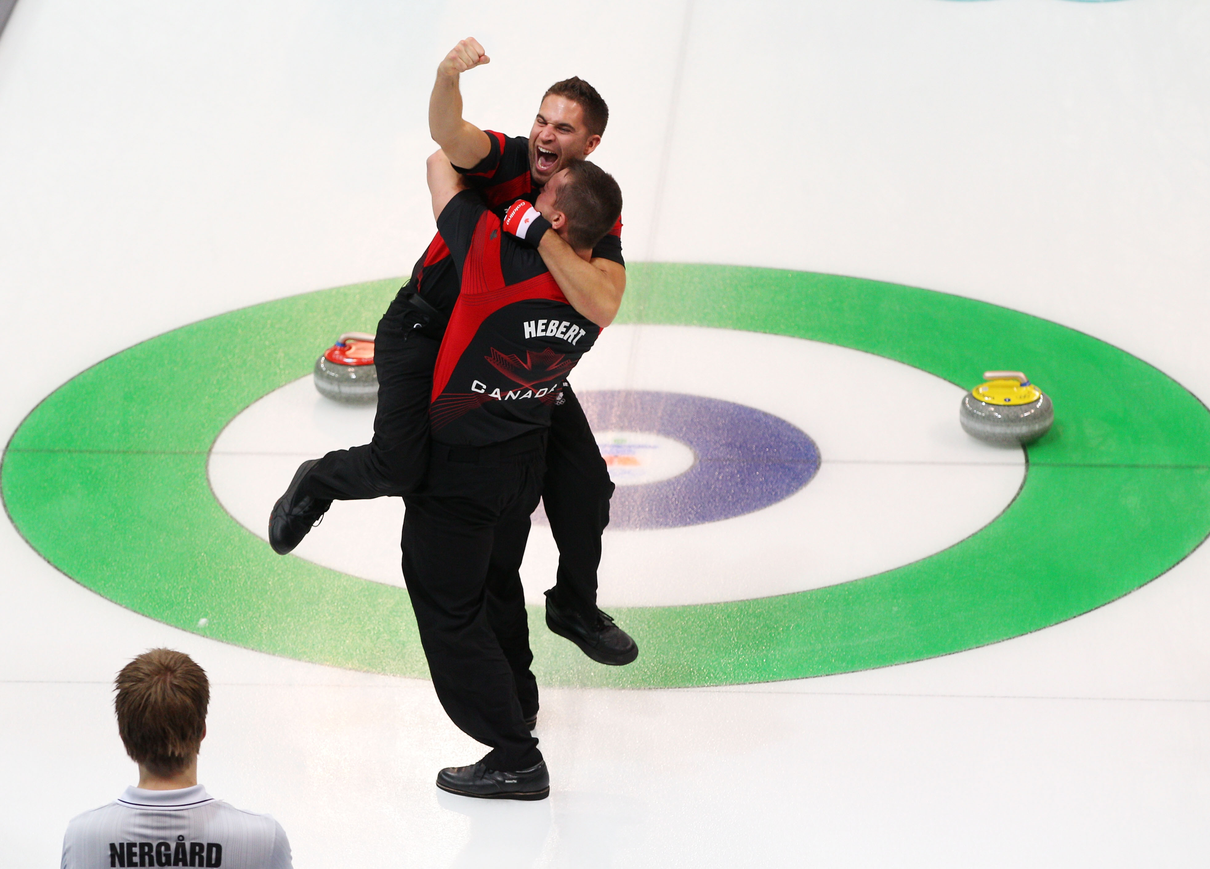 VANCOUVER, BC - FEBRUARY 27:  John Morris and Ben Hebert of Canada celebrates after winning the gold medal in front of Torger Nergaard of Norway after the Curling Men's Gold medal game on day 16 of the Vancouver 2010 Winter Olympics at the Vancouver Olymp