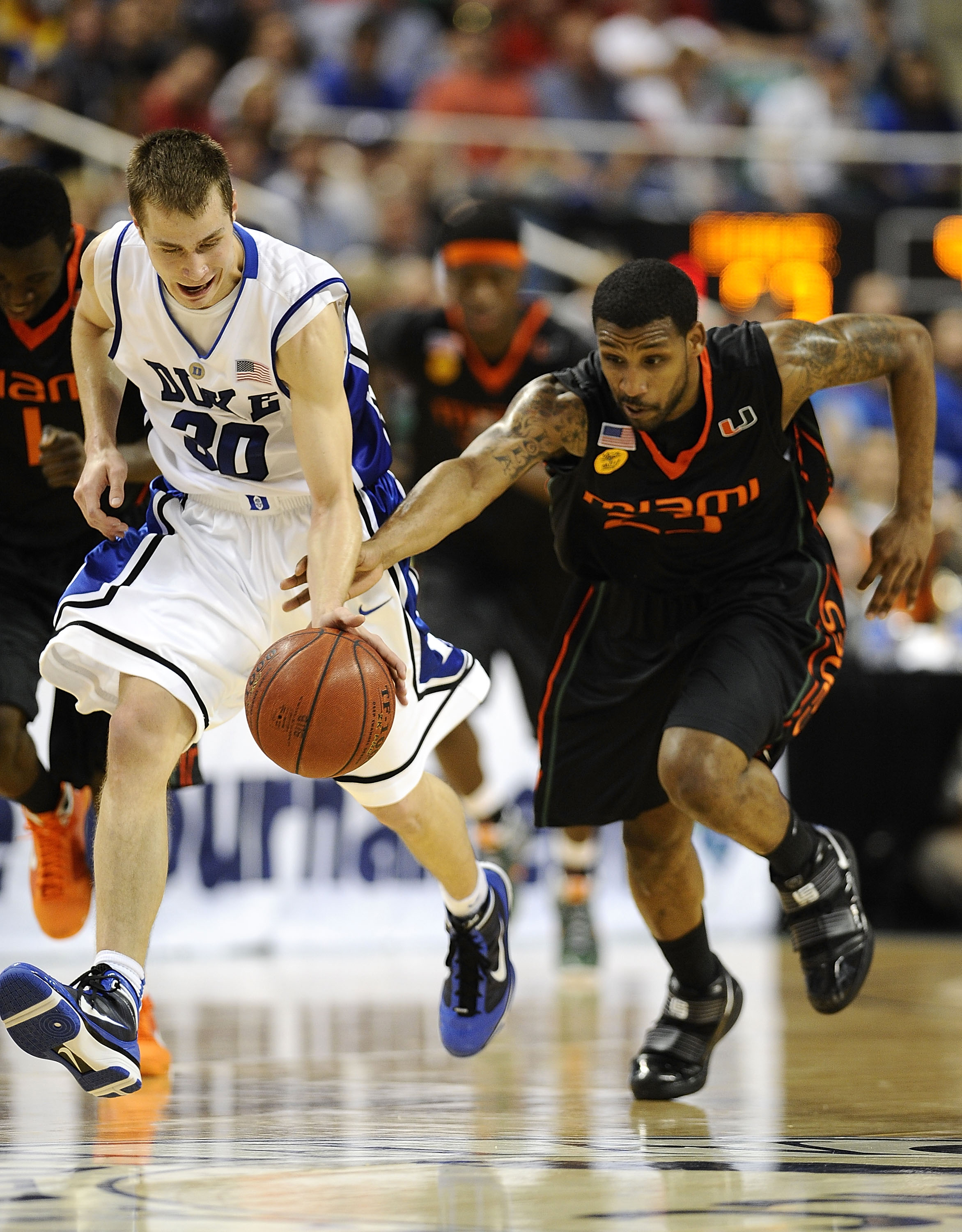 GREENSBORO, NC - MARCH 13:  Jon Scheyer #30 of the Duke Blue Devils and James Dews #23 of the University of Miami Hurricanes chase a ball in their semifinal game in the 2010 ACC Men's Basketball Tournament at the Greensboro Coliseum on on March 13, 2010 i