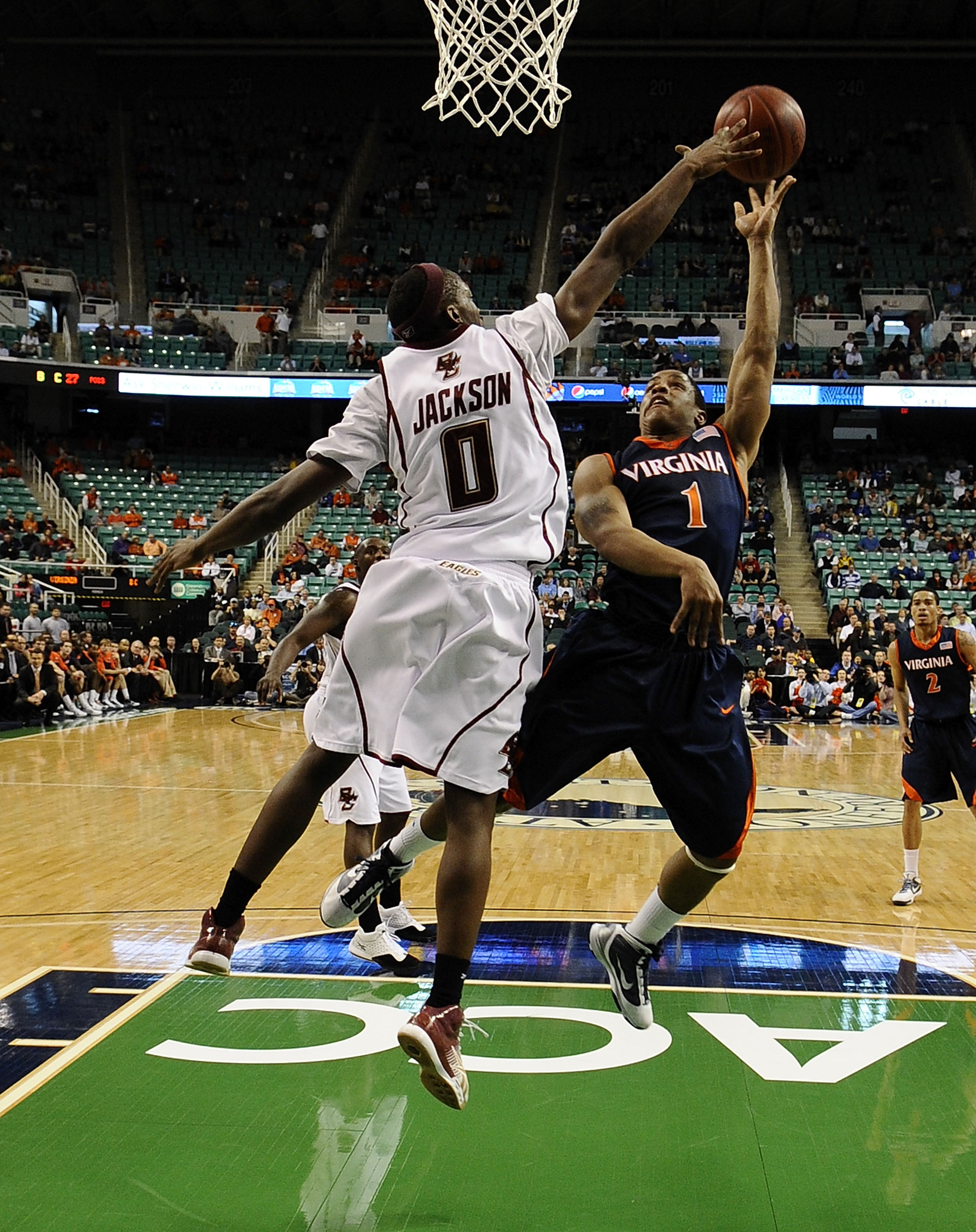 GREENSBORO, NC - MARCH 11:  Reggie Jackson #0 of the Boston College Eagles blocks a shot by Jontel Evans #1 of the University of Virginia Cavaliers in their first round game in the 2010 ACC Men's Basketball Tournament at the Greensboro Coliseum on March 1