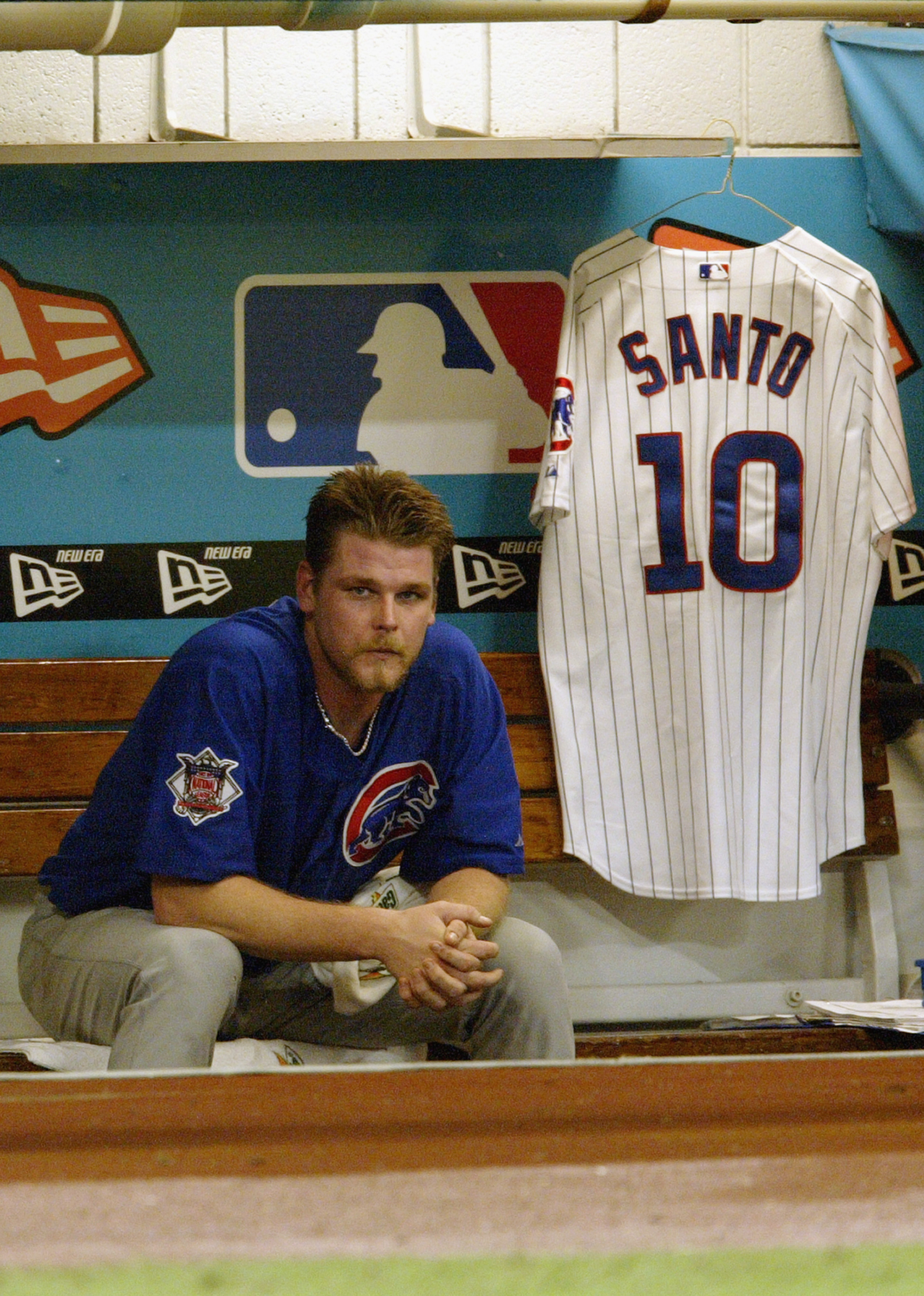 MIAMI - OCTOBER 10:  Kerry Wood #34 of the Chicago Cubs watches game three of the National League Championship Series against the Florida Marlins from the dugout as a uniform of Cub great Ron Santo #10 hangs beside him on October 10, 2003 at Pro Player St
