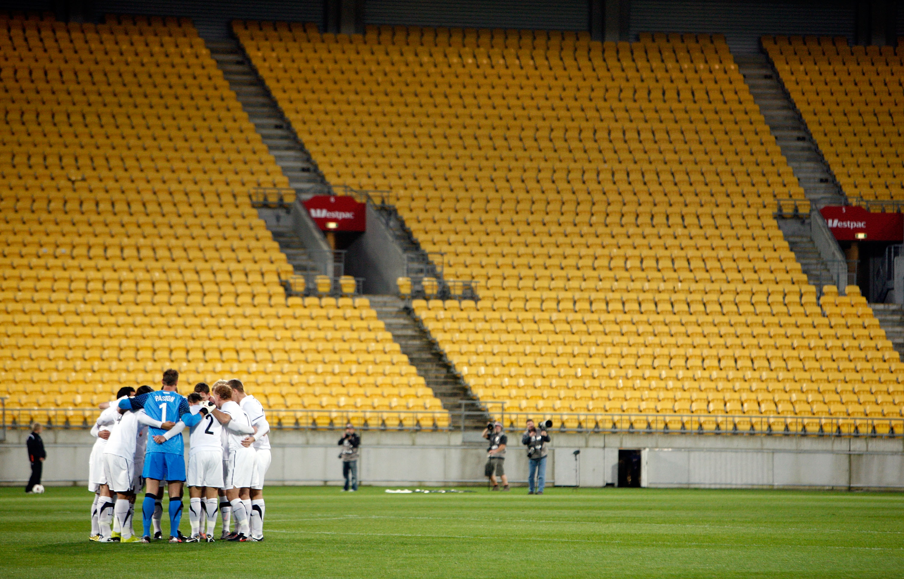 WELLINGTON, NEW ZEALAND - OCTOBER 12:  The All Whites form a huddle in front of empty stands during the International Friendly match between the New Zealand All Whites and Paraguay at Westpac Stadium on October 12, 2010 in Wellington, New Zealand.  (Photo