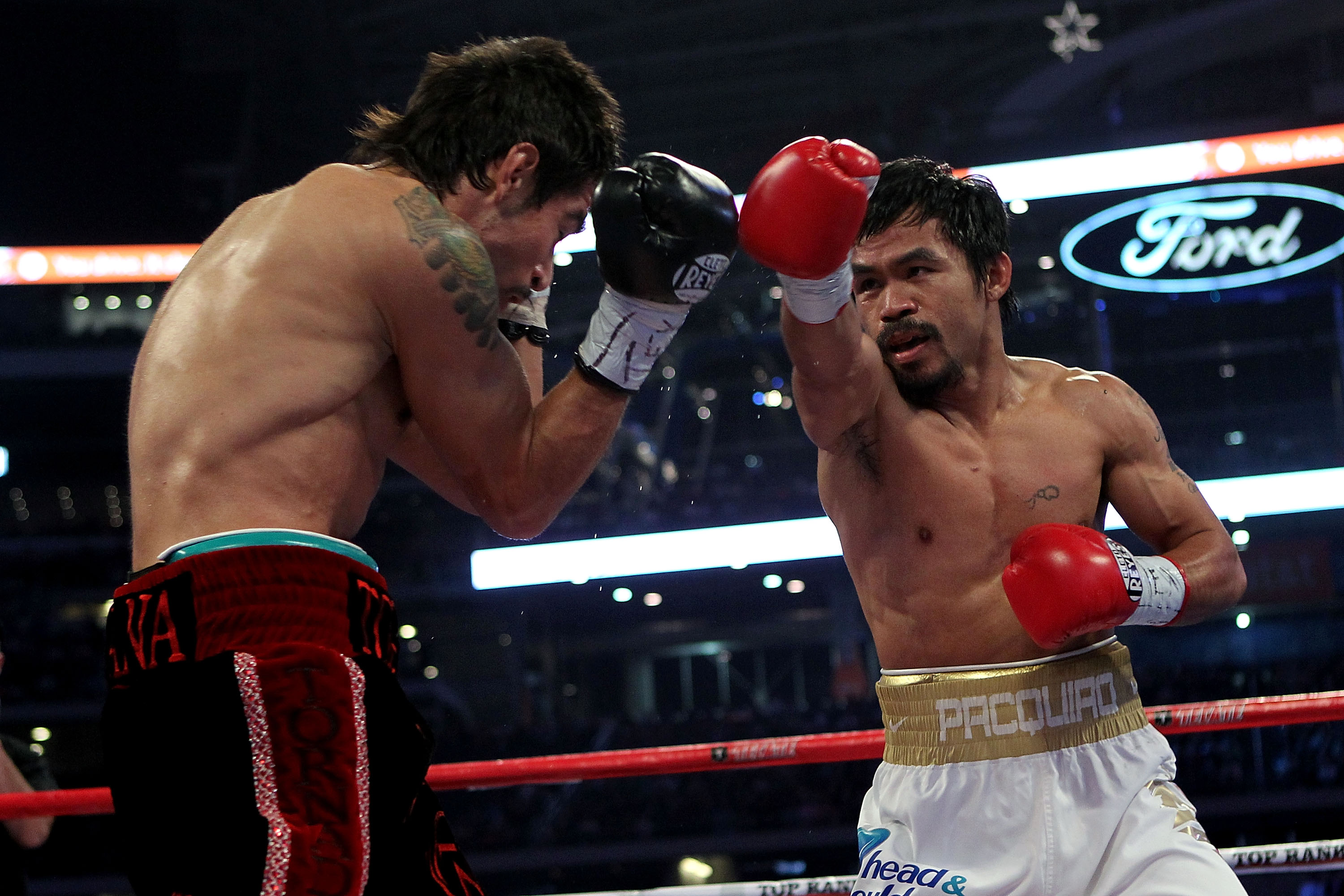 ARLINGTON, TX - NOVEMBER 13:  Manny Pacquiao (white trunks) of the Philippines throws a punch against Antonio Margarito (black trunks) of Mexico during their WBC World Super Welterweight Title bout at Cowboys Stadium on November 13, 2010 in Arlington, Tex