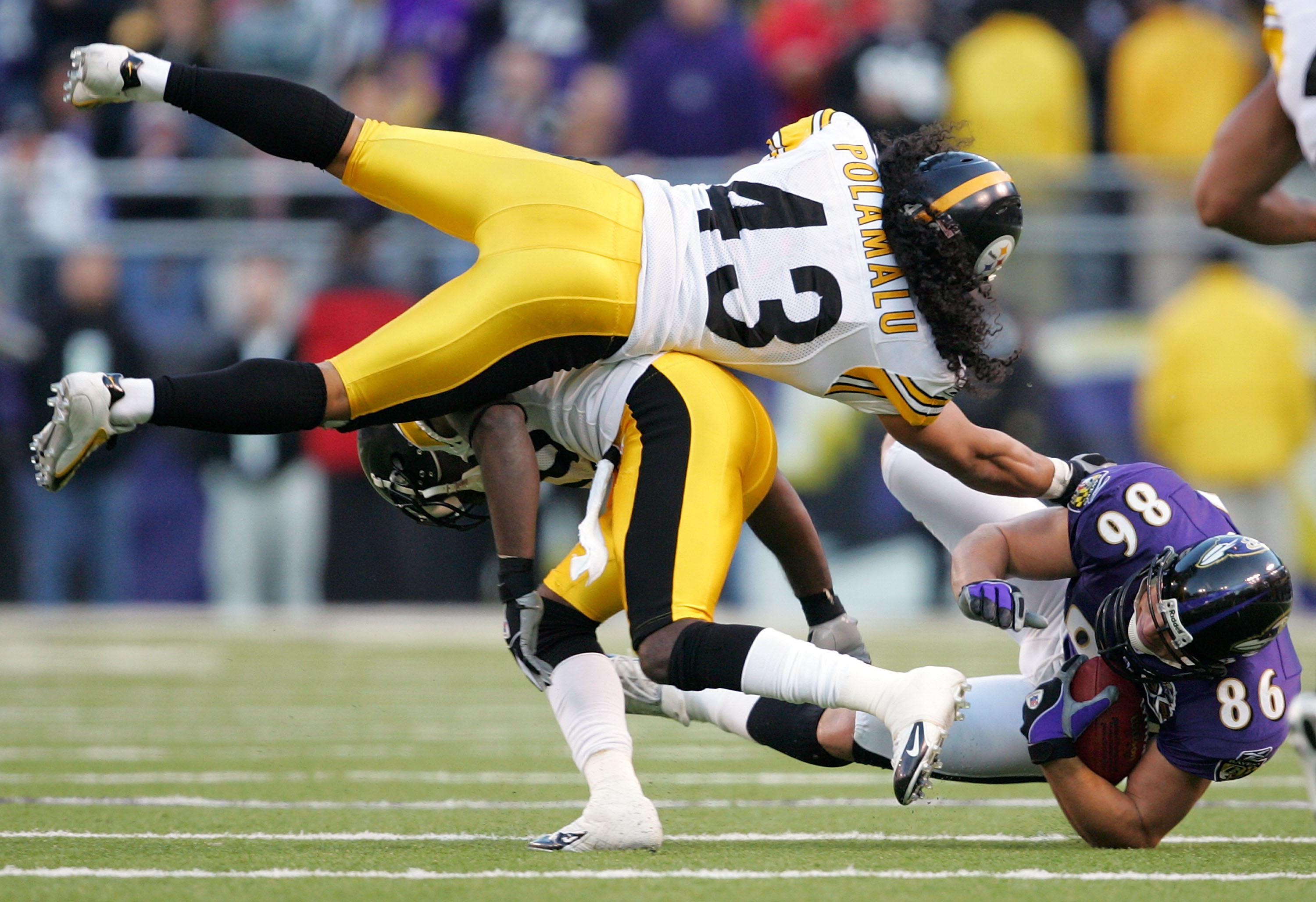 BALTIMORE - NOVEMBER 20:  Troy Polamalu #43 of the Pittsburgh Steelers leaps over the back of teammate Bryant McFadden #20 as he tries to tackle Todd Heap #86 of the Baltimore Ravens during the second half of the game on November 20, 2005 at M&T Bank Stad