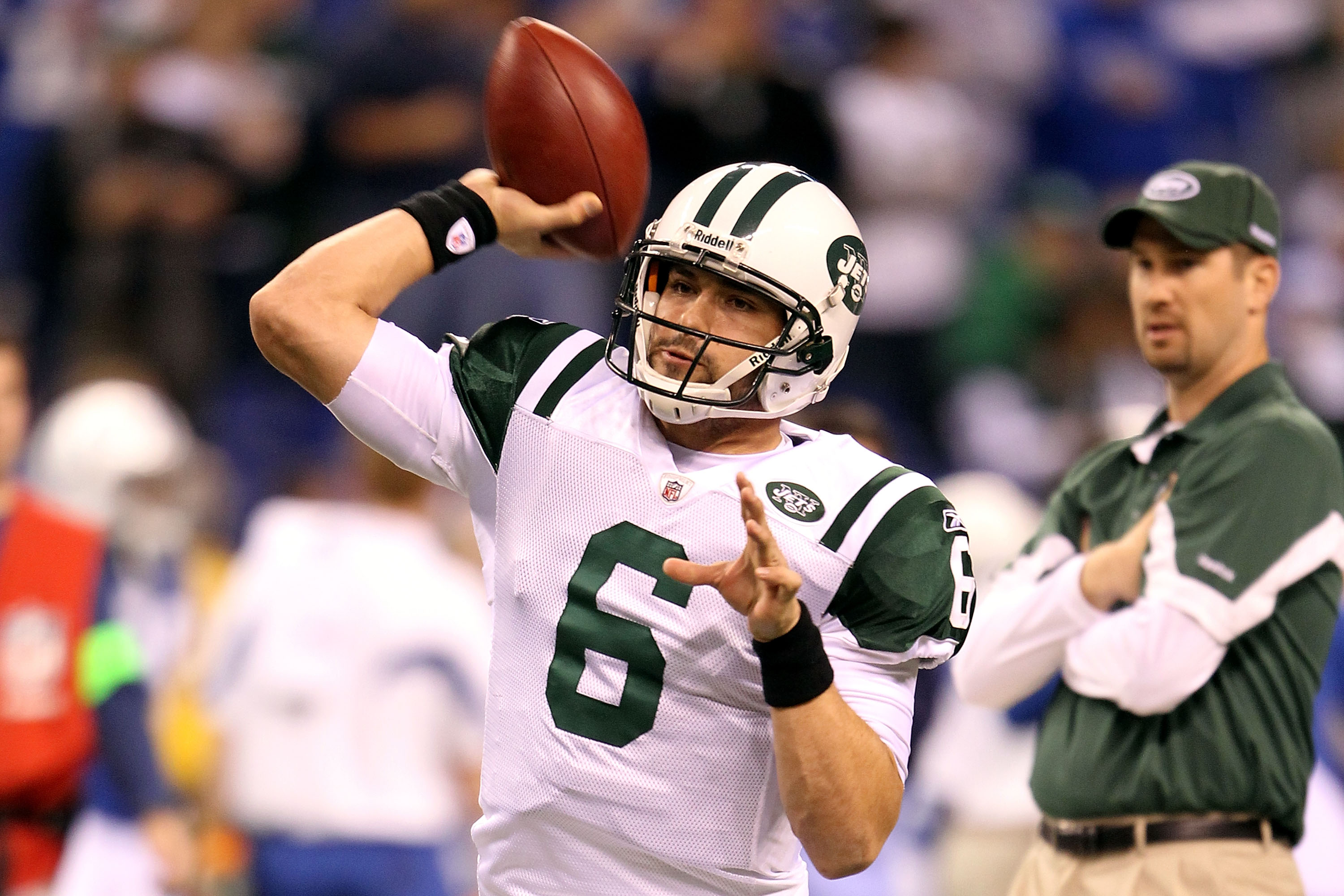 INDIANAPOLIS, IN - JANUARY 08:  Quarterback Mark Sanchez #6 of the New York Jets warms up as offensive coordinator Brian Schottenheimer looks on against the Indianapolis Colts during their 2011 AFC wild card playoff game at Lucas Oil Stadium on January 8,