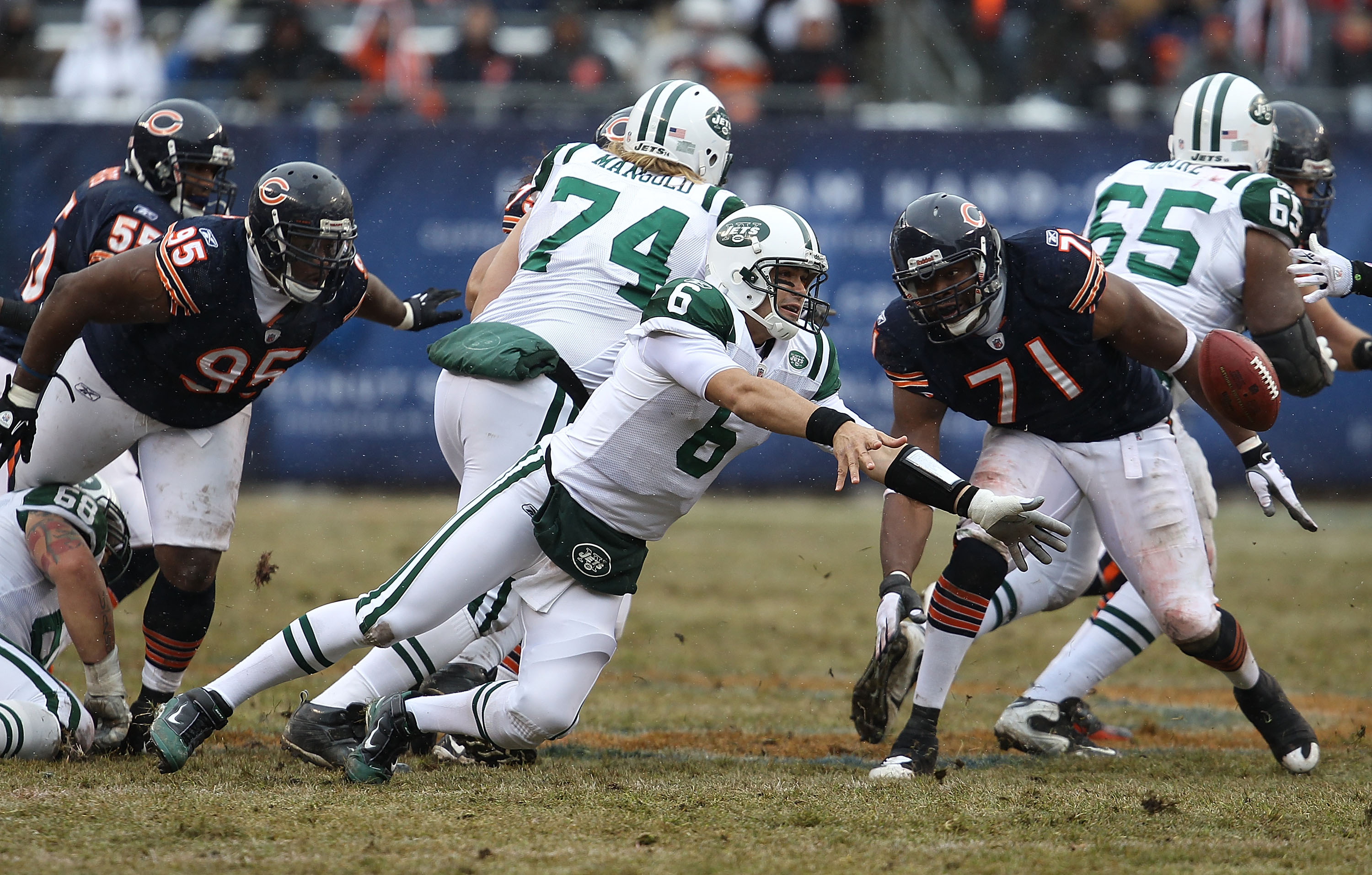 CHICAGO, IL - DECEMBER 26: Mark Sanchez #6 of the New York Jets slips as he tosses the ball to a running back as Anthony Adams #95 and Israel Idonije #71 of the Chicago Bears rush at Soldier Field on December 26, 2010 in Chicago, Illinois. The Bears defea