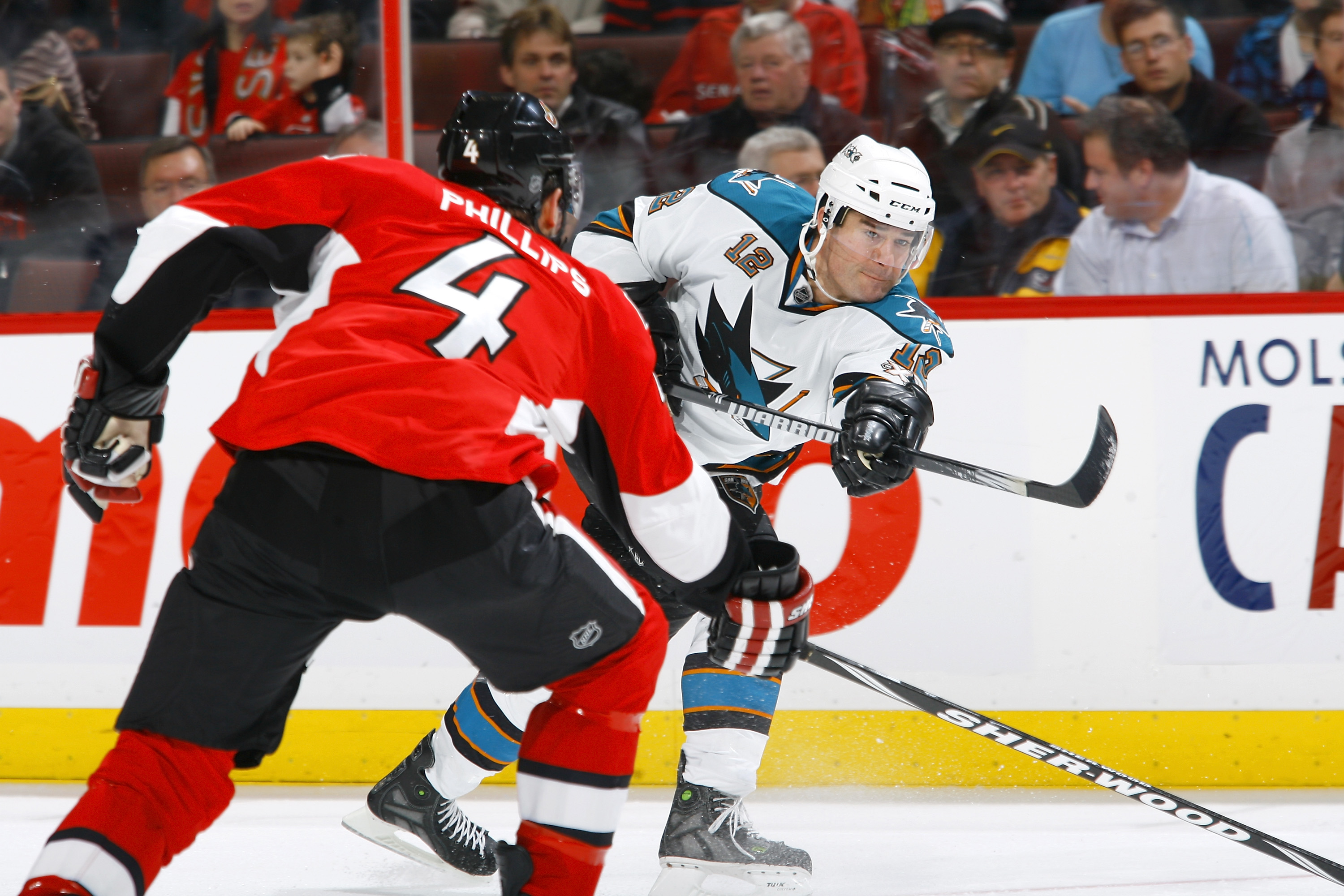 OTTAWA, ON - DECEMBER 02:  Patrick Marleau #12 of the San Jose Sharks fires a slapshot past defender Chris Phillips #4 of the Ottawa Senators in a game at Scotiabank Place on December 2, 2010 in Ottawa, Ontario, Canada.  (Photo by Phillip MacCallum/Getty