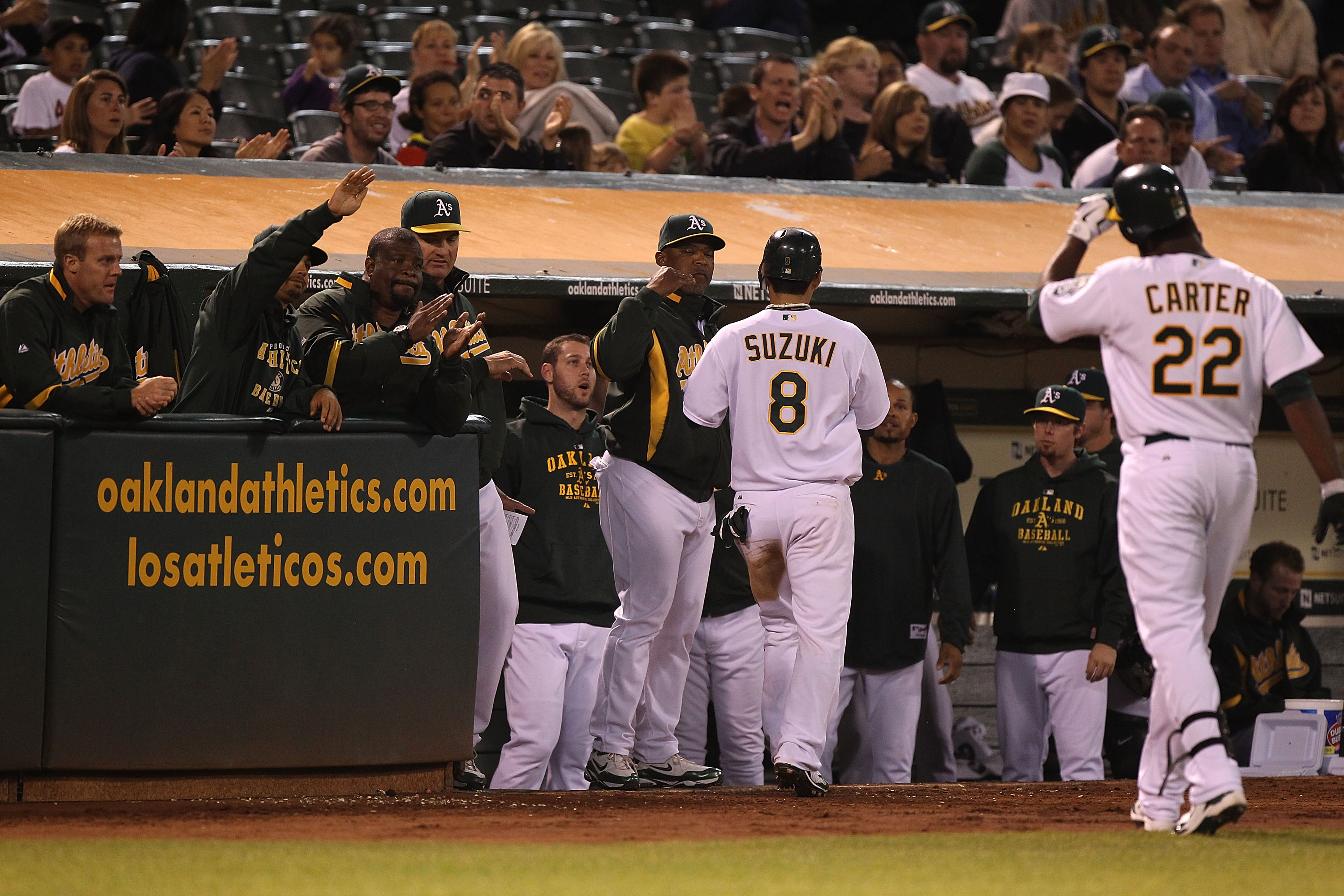 OAKLAND, CA - SEPTEMBER 23:  Chirs Carter #22 of the Oakland Athletics celebrates with Kurt Suzuki #8 after hitting an RBI sacrafice fly against the Texas Rangers in the fourth inning during a Major League Baseball game at the Oakland-Alameda County Colis