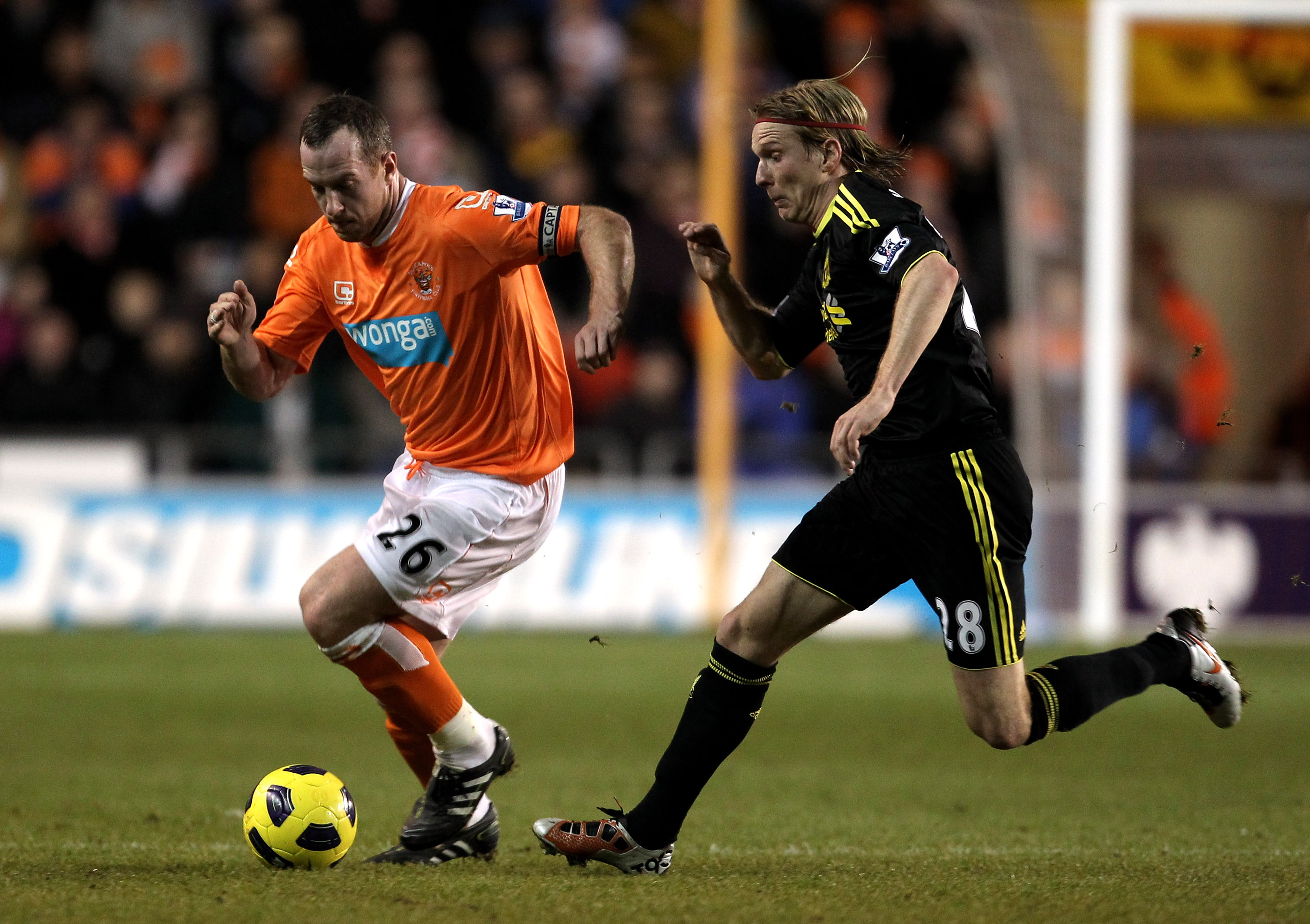 BLACKPOOL, ENGLAND - JANUARY 12:  Charlie Adam of Blackpool is pursued by Christian Poulsen of Liverpool during the Barclays Premier League match between Blackpool and Liverpool at Bloomfield Road on January 12, 2011 in Blackpool, England.  (Photo by Alex