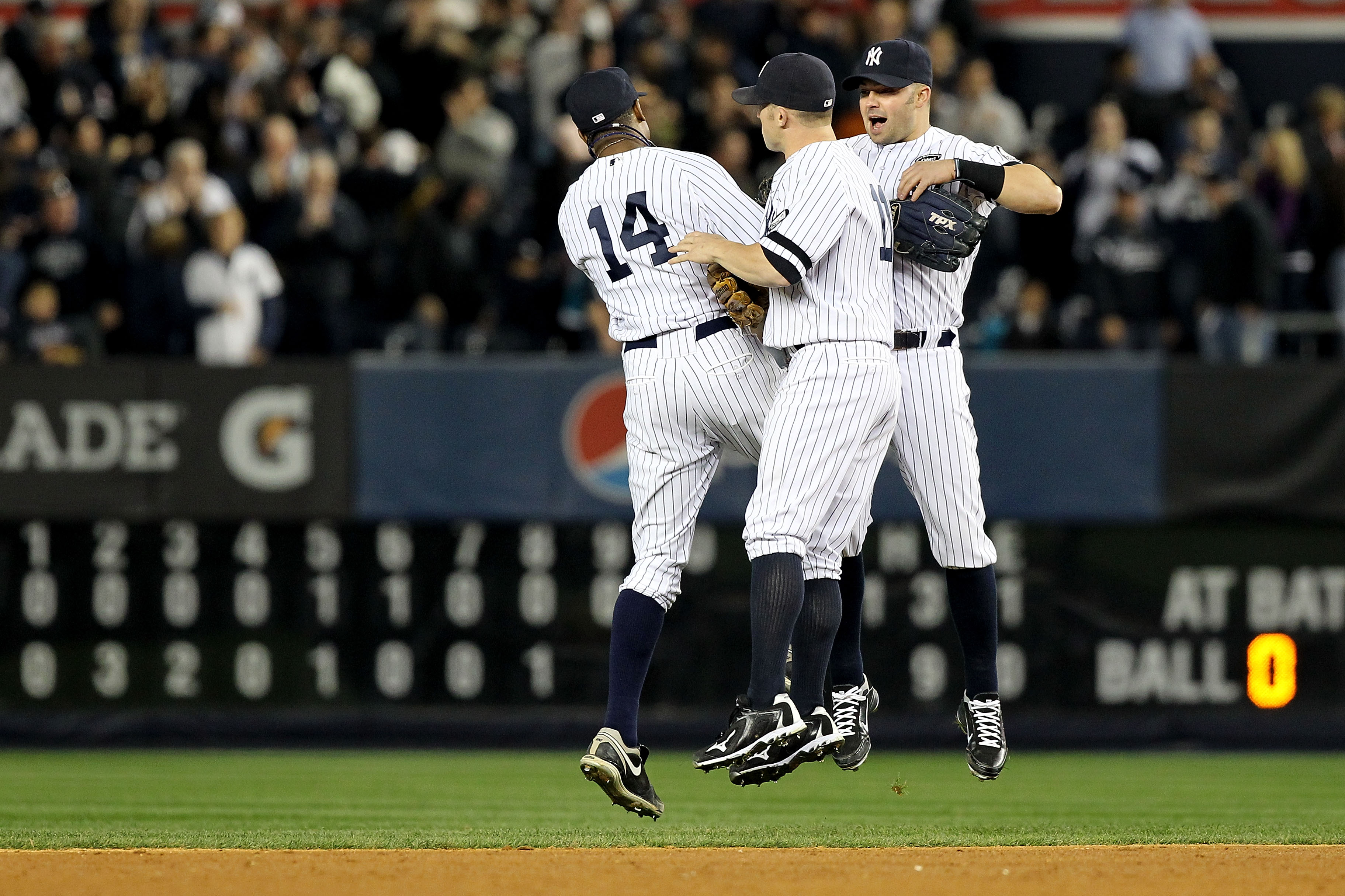 NEW YORK - OCTOBER 20:  Curtis Granderson #14, Brett Gardner #11 and Nick Swisher #33 of the New York Yankees celebrate after the Yankees won 7-2 against the Texas Rangers in Game Five of the ALCS during the 2010 MLB Playoffs at Yankee Stadium on October
