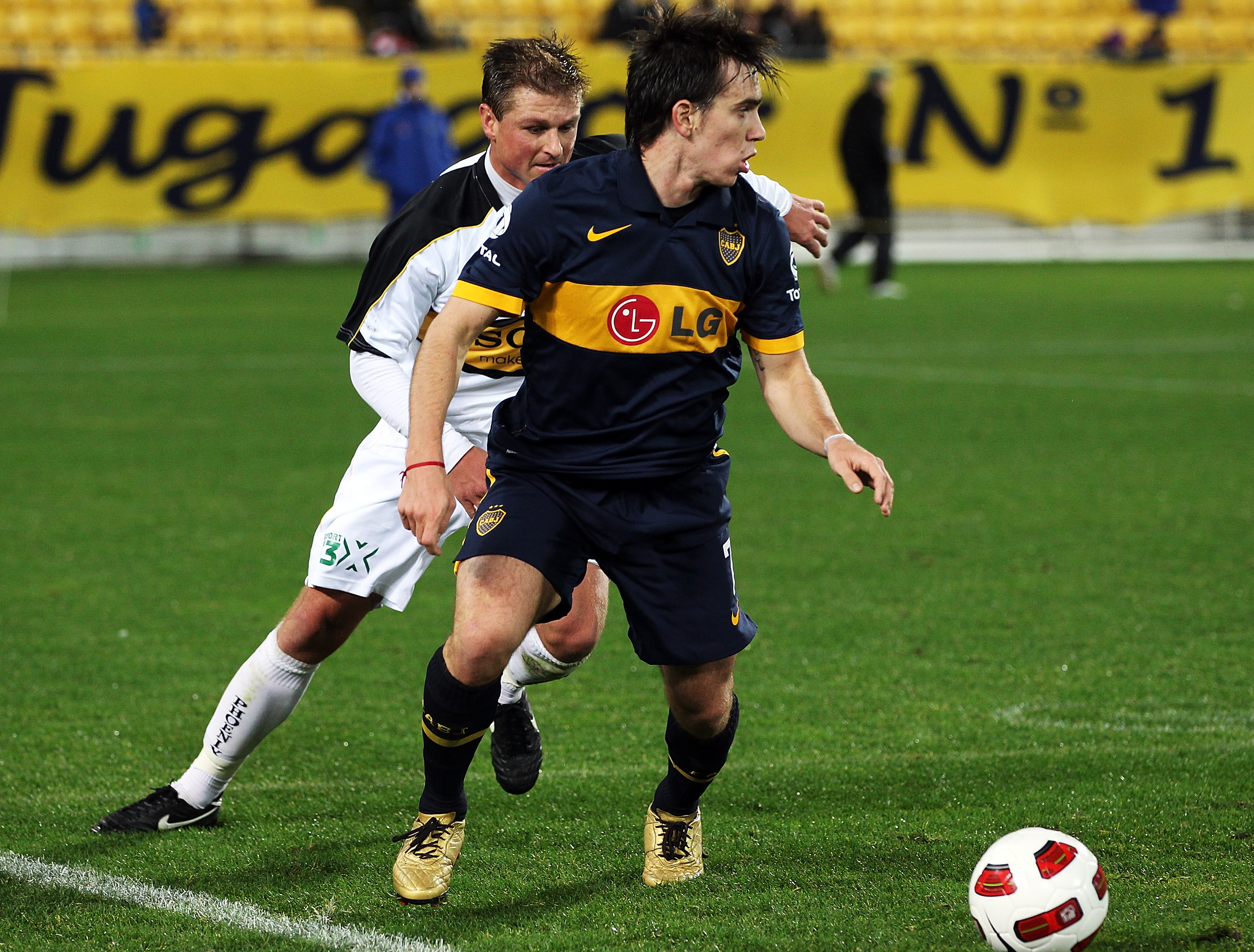 WELLINGTON, NEW ZEALAND - JULY 23:  Pablo Mouche of the Boca Juniors gets past Ben Sigmund of the Phoenix during the pre-season friendly match between Wellington Phoenix and Boca Juniors at Westpac Stadium on July 23, 2010 in Wellington, New Zealand.  (Ph