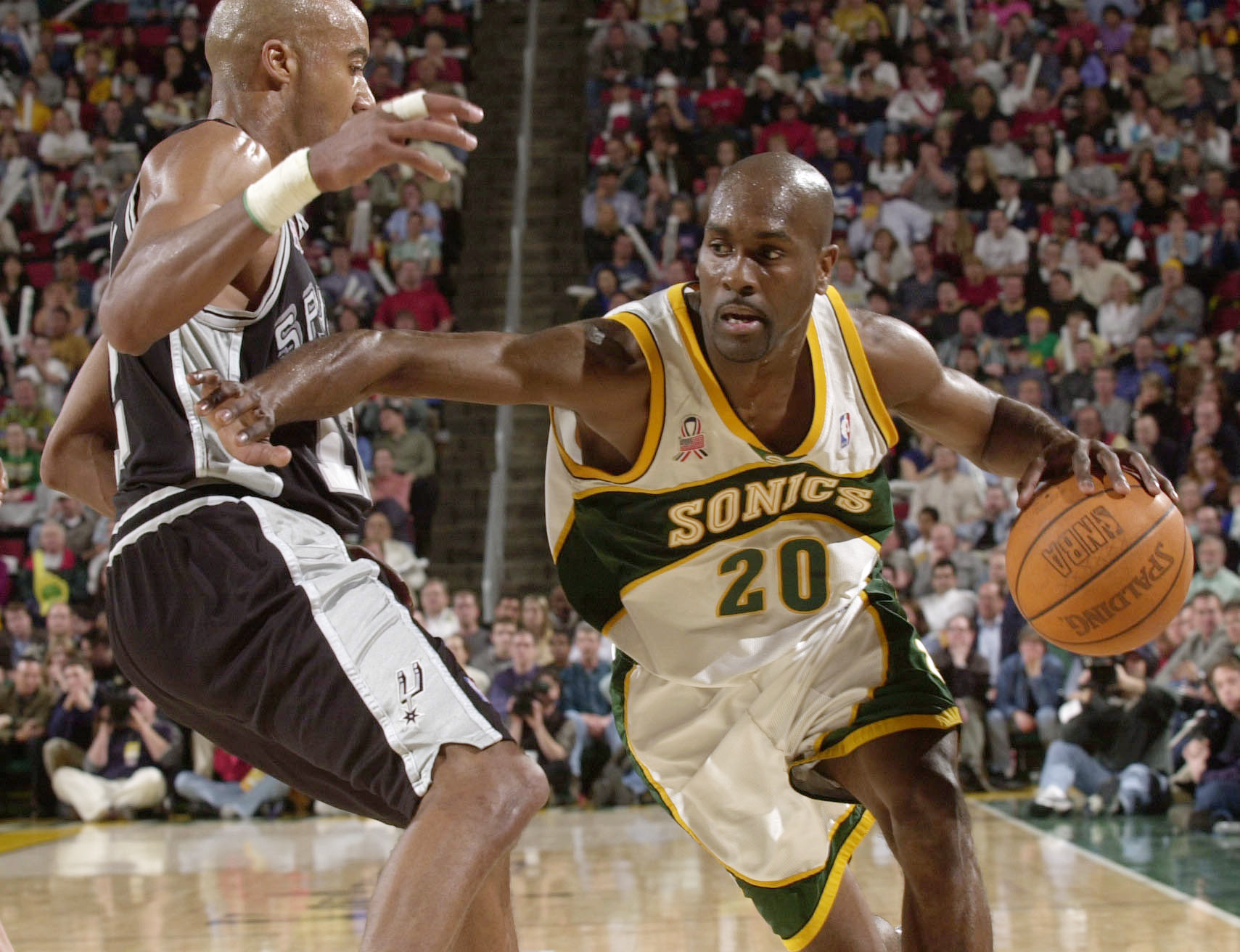 SEATTLE - MAY 1:  Gary Payton #20 of the Seattle SuperSonics drives against Bruce Bowen #12 of the San Antonio Spurs game 4 of the Western Conference quarterfinal series during the 2002 NBA Playoffs at Key Arena in Seattle, Washington.   NOTE TO USER: Use