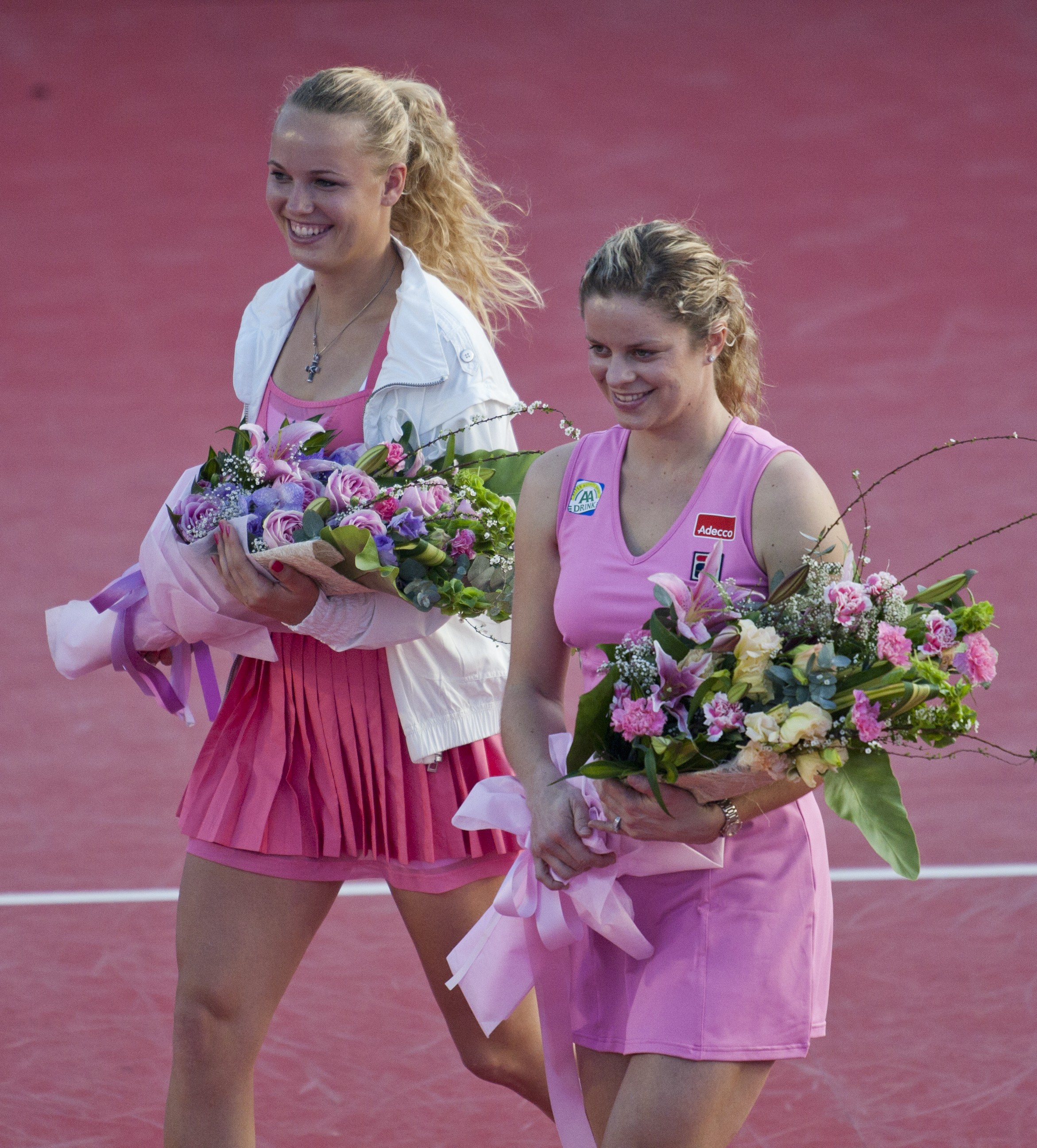 HUA HIN, THAILAND - JANUARY 01:    Caroline Wozniacki of Denmark and Kim Clijsters of Belgium hold the bouquets of flowers before their exhibition match at Centenial Park on January 1, 2011 in Hua Hin, Thailand.  (Photo by Athit Perawongmetha/Getty Images