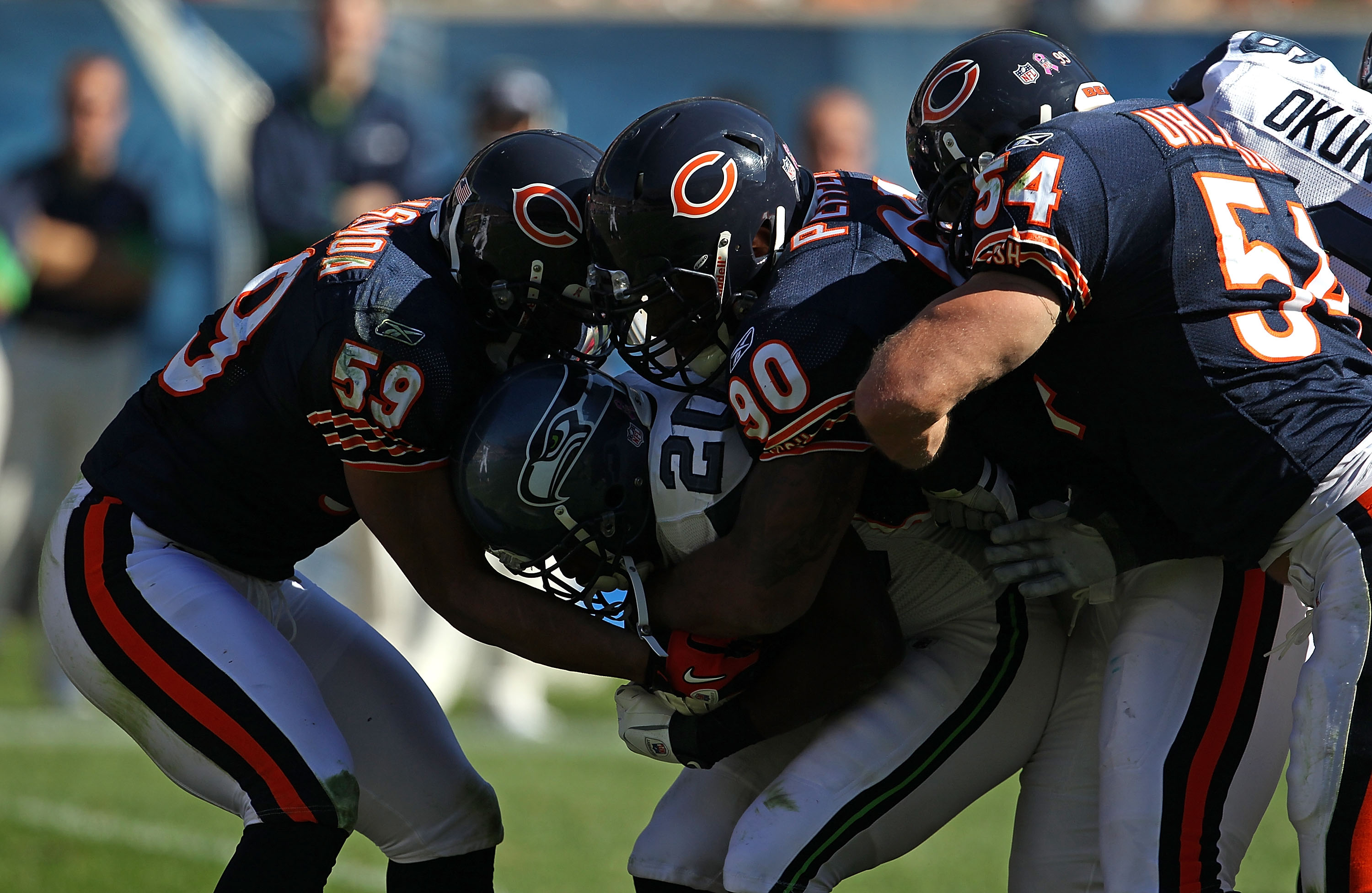 CHICAGO - OCTOBER 17: Justin Forsett #20 of the Seattle Seahawks is tackled by (L-R) Pia Tinoisamoa #59, Julius Peppers #90 and Brian Urlacher #54 of the Chicago Bears at Soldier Field on October 17, 2010 in Chicago, Illinois. The Seahawks defeated the Be