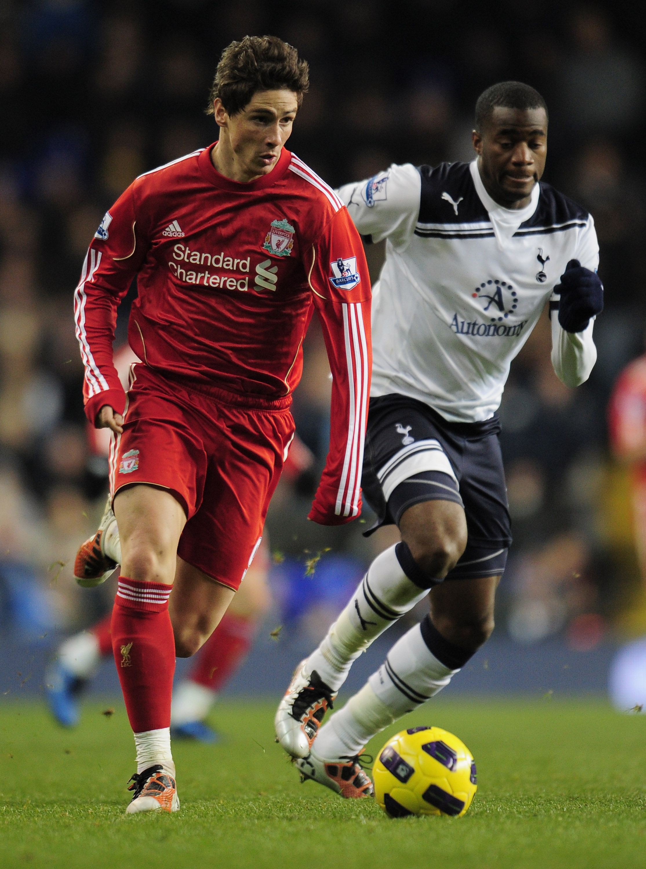 LONDON, ENGLAND - NOVEMBER 28:  Fernando Torres of Liverpool runs with the ball as he is closed down by Sebastien Bassong of Tottenham Hotspur during the Barclays Premier League match between Tottenham Hotspur and Liverpool at White Hart Lane on November