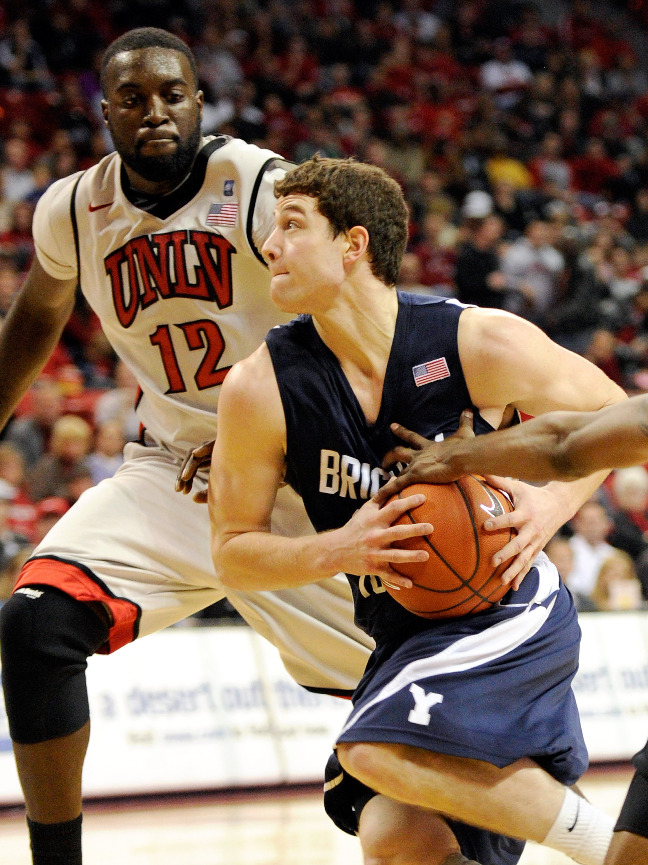 LAS VEGAS, NV - JANUARY 05:  Jimmer Fredette #32 of the Brigham Young University Cougars drives against Brice Massamba #12 of the UNLV Rebels during their game at the Thomas & Mack Center January 5, 2011 in Las Vegas, Nevada. BYU won 89-77.  (Photo by Eth