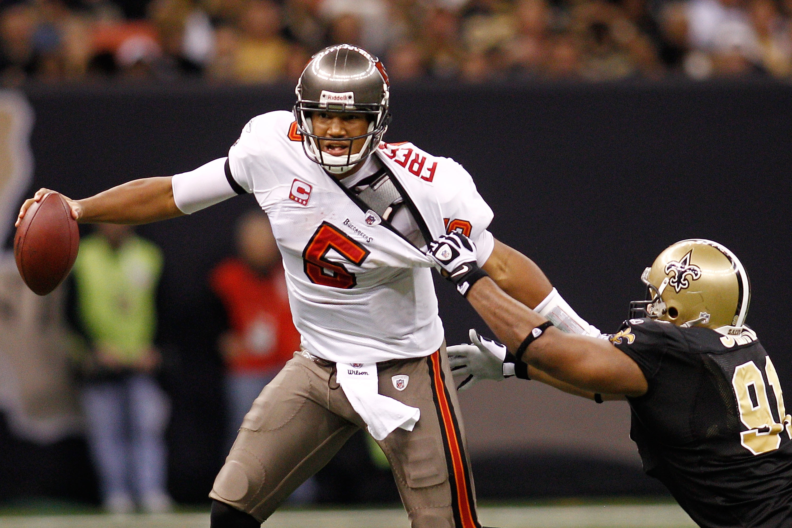 NEW ORLEANS, LA - JANUARY 02:  Quarterback Josh Freeman #5 of the Tampa Bay Buccaneers avoids a tackle by Will Smith #91 of the New Orleans Saints at the Louisiana Superdome on January 2, 2011 in New Orleans, Louisiana.   The Buccaneers defeated the Saint