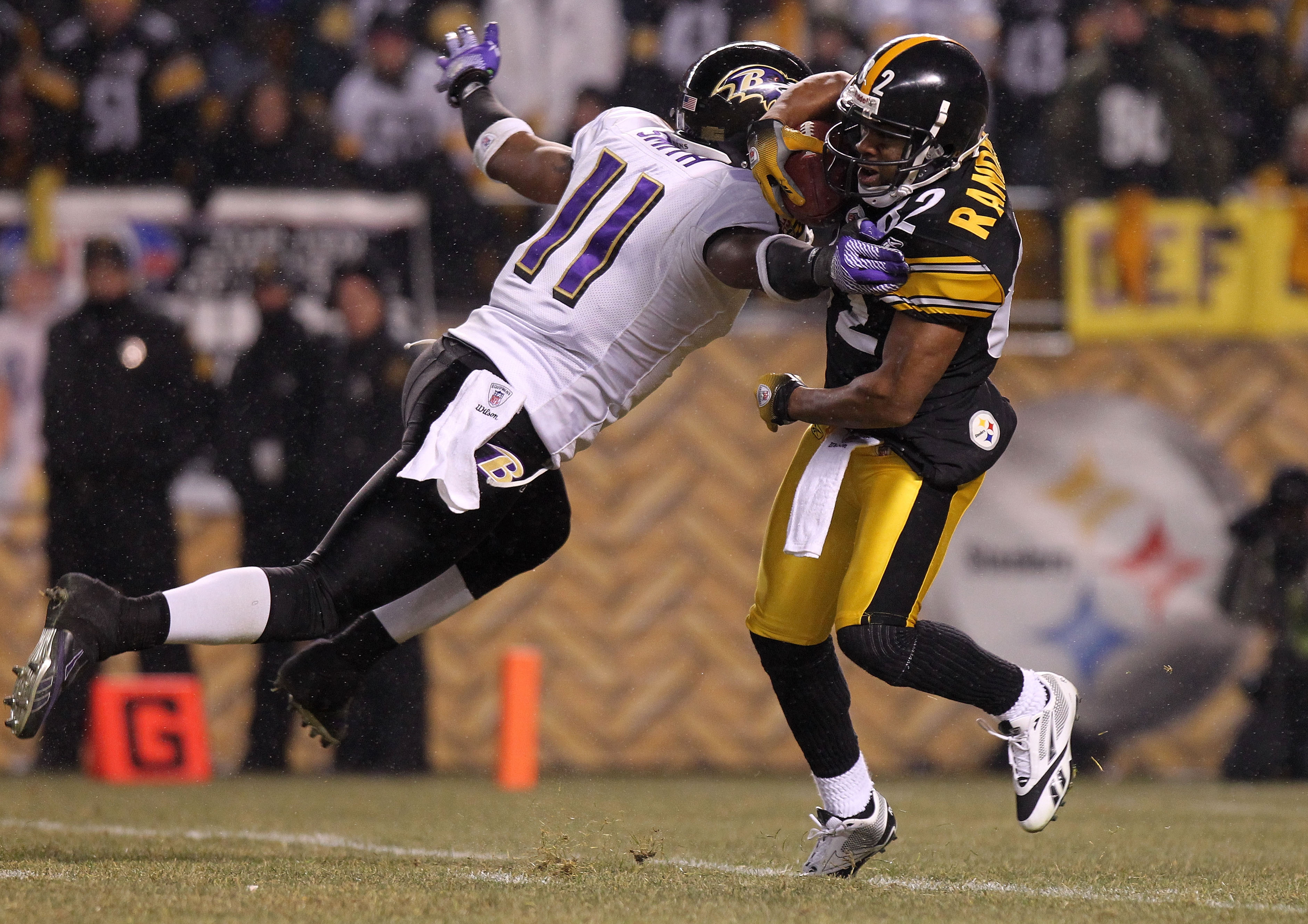 PITTSBURGH, PA - JANUARY 15:  Marcus Smtih #11 of the Baltimore Ravens tackles Antwaan Randle El #82 of the Pittsburgh Steelers during a kick return in the AFC Divisional Playoff Game at Heinz Field on January 15, 2011 in Pittsburgh, Pennsylvania.  (Photo