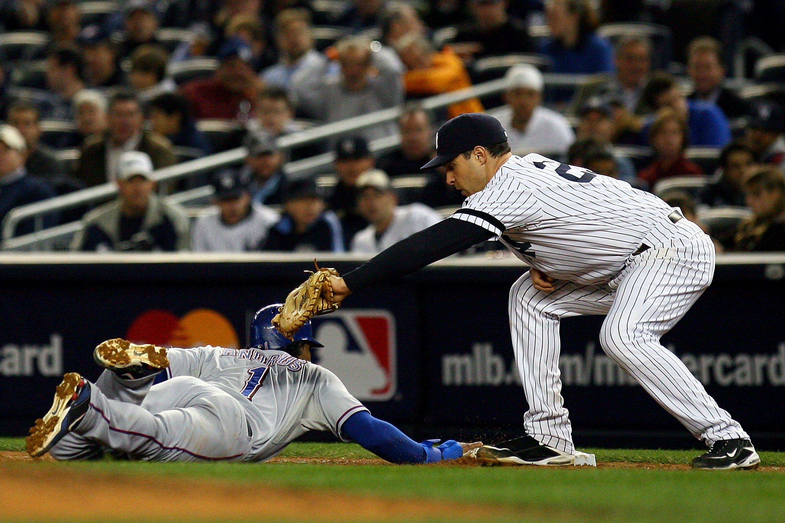 NEW YORK - OCTOBER 19:  Elvis Andrus #1 of the Texas Rangers slides safely into first under the tag of Mark Teixeira #25 of the New York Yankees in Game Four of the ALCS during the 2010 MLB Playoffs at Yankee Stadium on October 19, 2010 in the Bronx borou