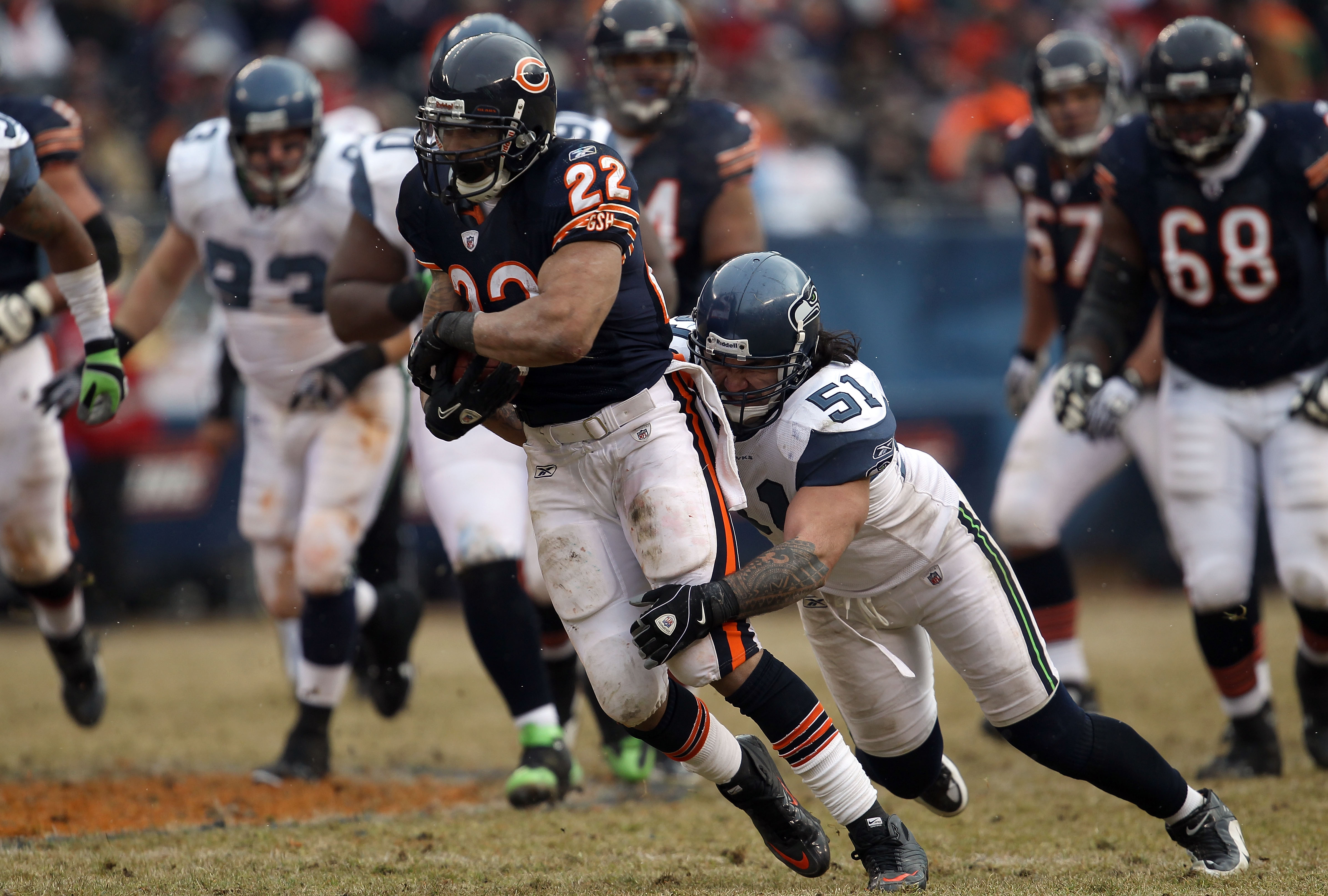 CHICAGO, IL - JANUARY 16:  Running back Matt Forte #22 of the Chicago Bears runs the ball as Lofa Tatupu #51 of the Seattle Seahawks attempts to tackle him from behind in the 2011 NFC divisional playoff game at Soldier Field on January 16, 2011 in Chicago