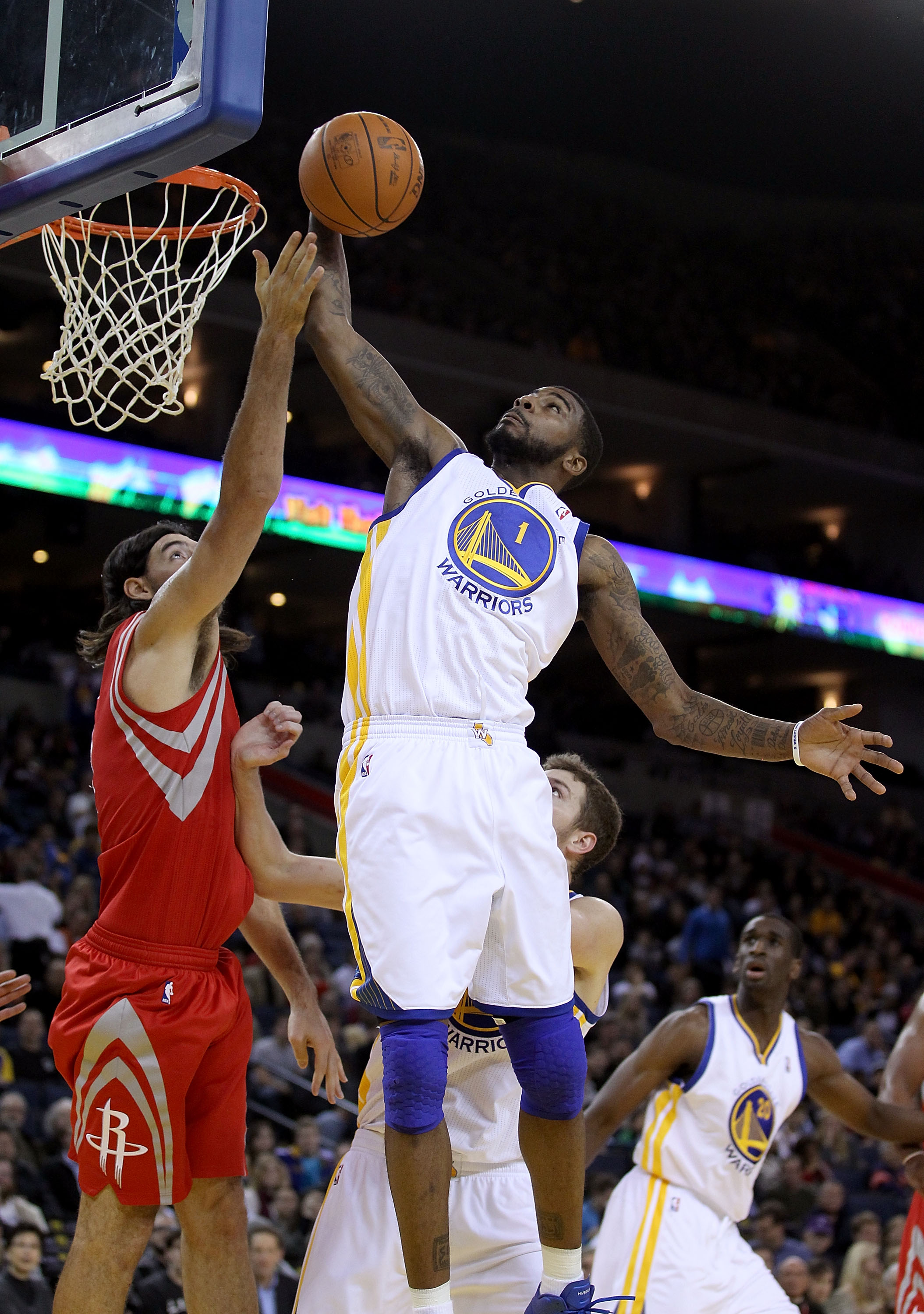 OAKLAND, CA - DECEMBER 20:  Dorell Wright #1 of the Golden State Warriors grabs a rebound over Luis Scola #4 of the Houston Rockets at Oracle Arena on December 20, 2010 in Oakland, California. NOTE TO USER: User expressly acknowledges and agrees that, by