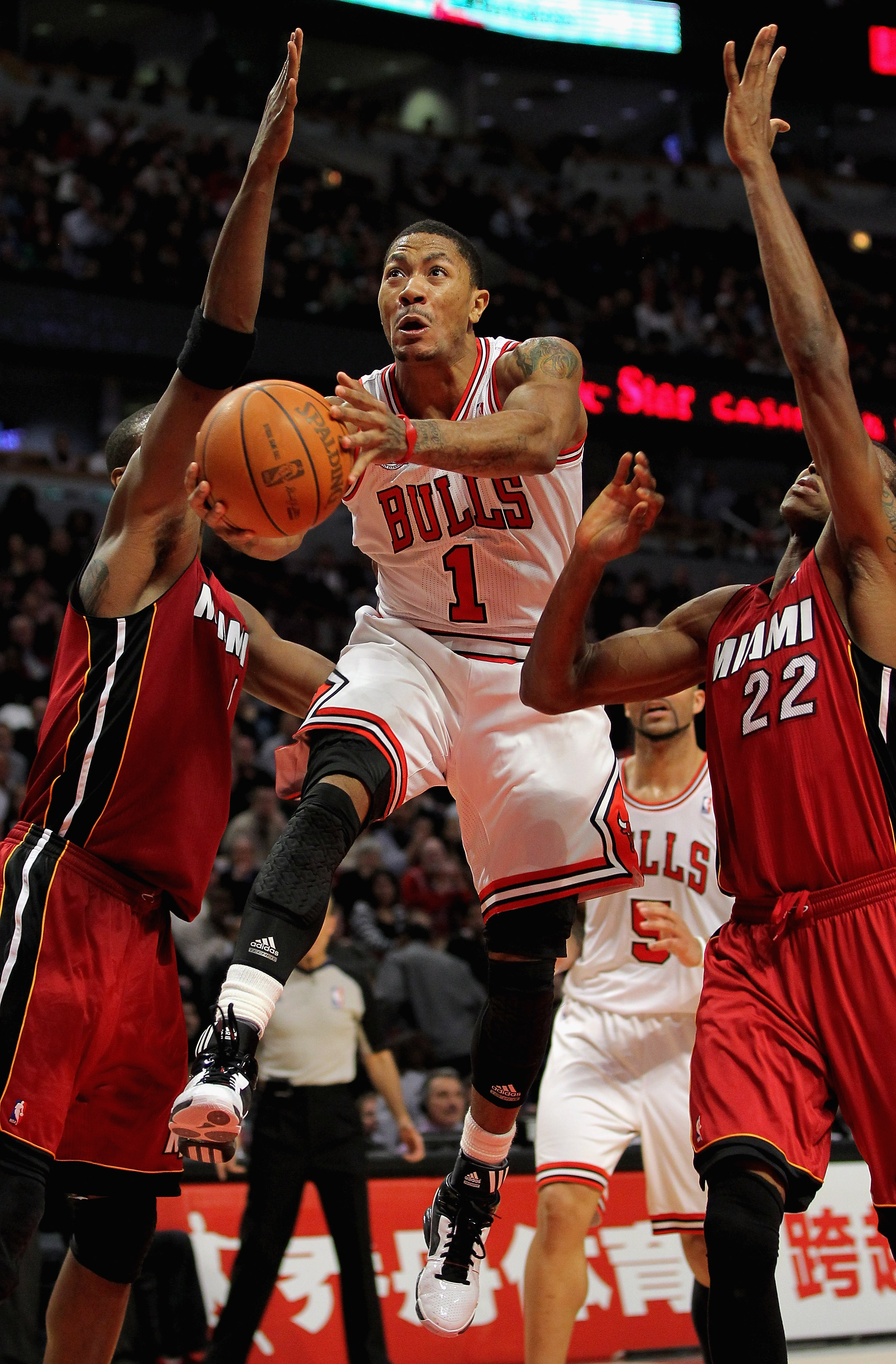 CHICAGO, IL - JANUARY 15:  Derrick Rose #1 of the Chicago Bulls lays up a shot between Chris Bosh #1 and James Jones #22 of the Miami Heat at the United Center on January 15, 2011 in Chicago, Illinois. NOTE TO USER: User expressly acknowledges and agrees