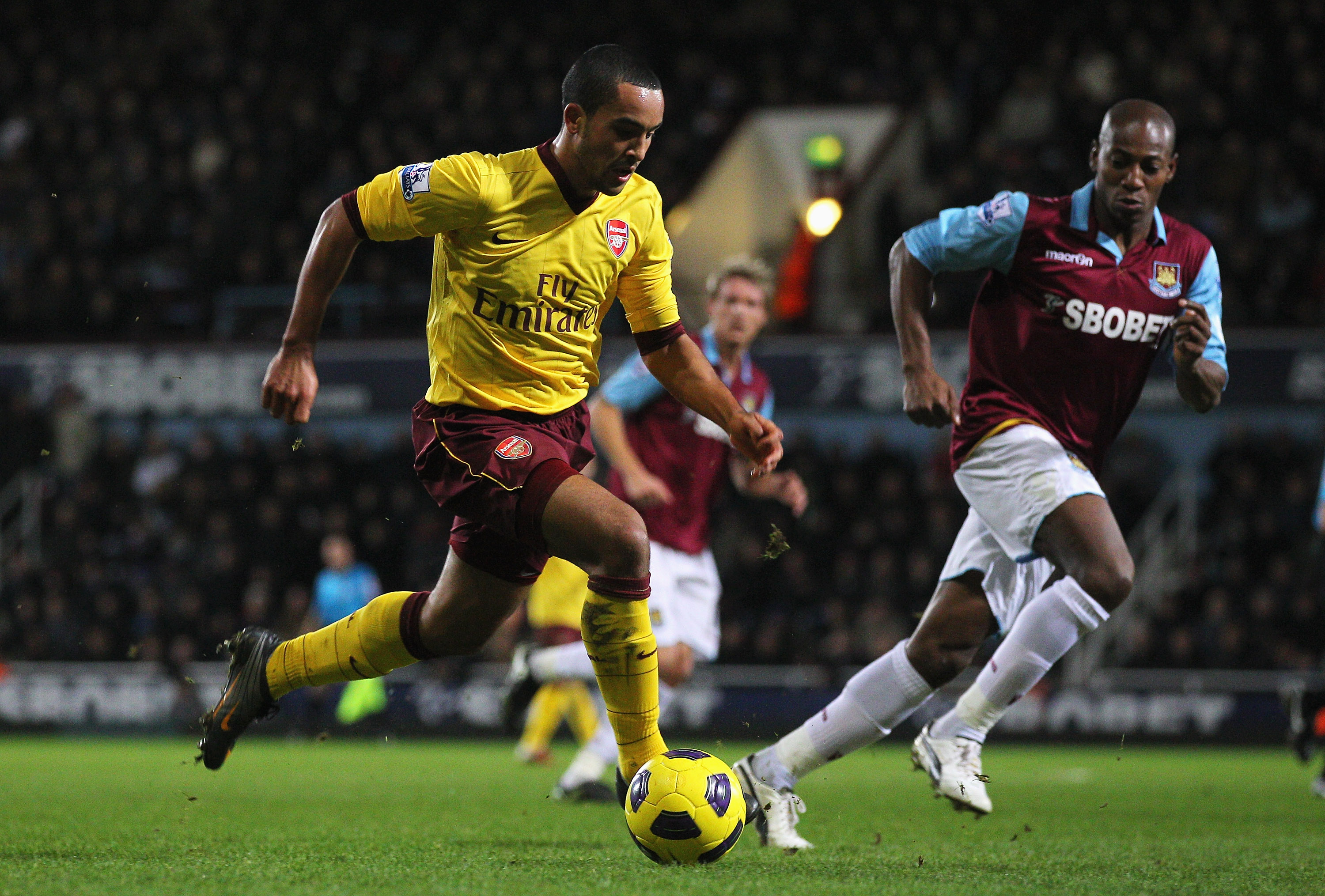 LONDON, ENGLAND - JANUARY 15:  Theo Walcott of Arsenal takes the ball past Luis Boa Morte of West Ham United during the Barclays Premier League match between West Ham United and Arsenal at the Boleyn Ground on January 15, 2011 in London, England.  (Photo
