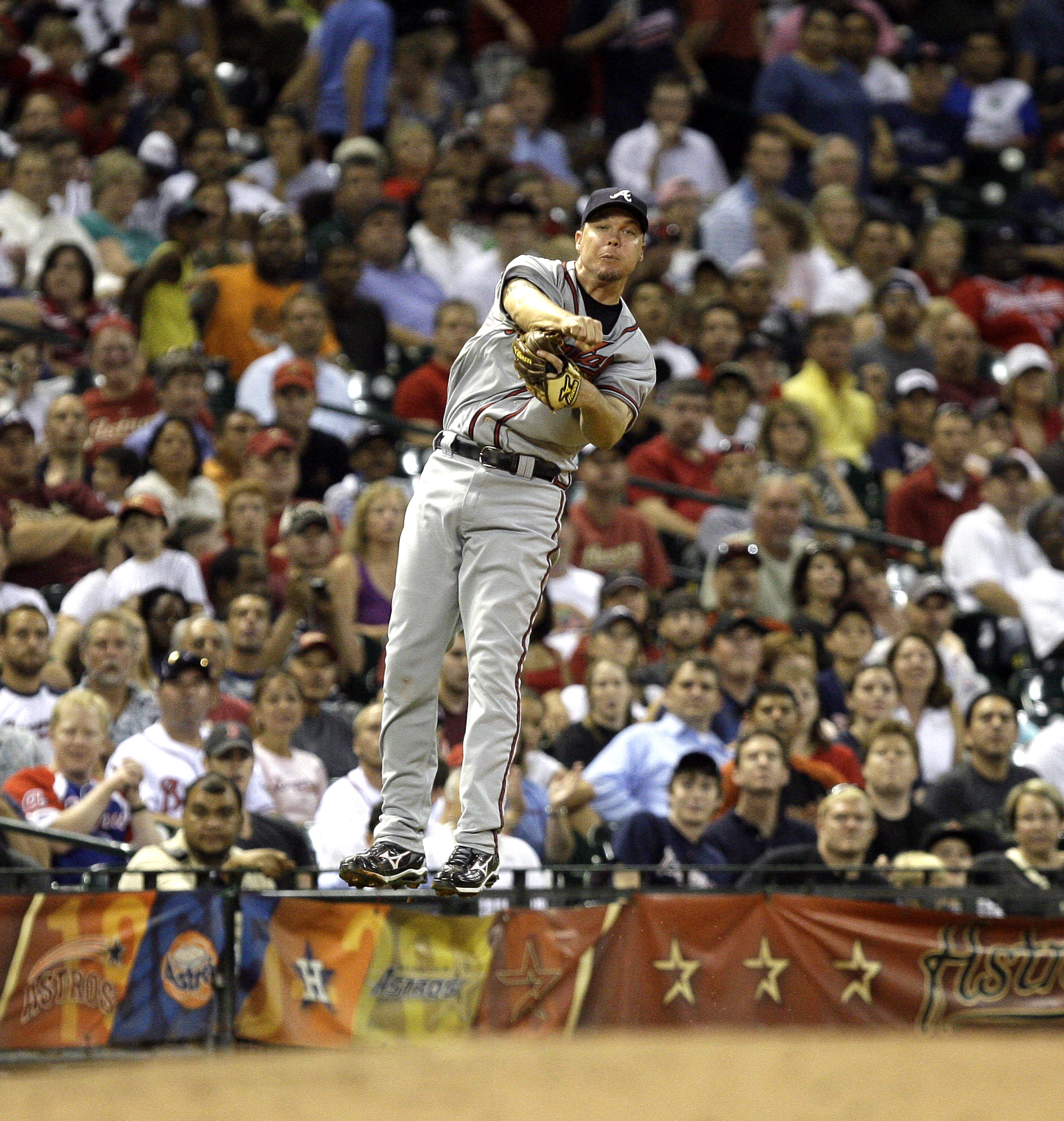 HOUSTON - AUGUST 10:  Third baseman Chipper Jones #10 of the Atlanta Braves throws out Hunter Pence of the Houston Astros from deep behind the base at Minute Maid Park on August 10, 2010 in Houston, Texas. Jones left the game after injuring himself on the