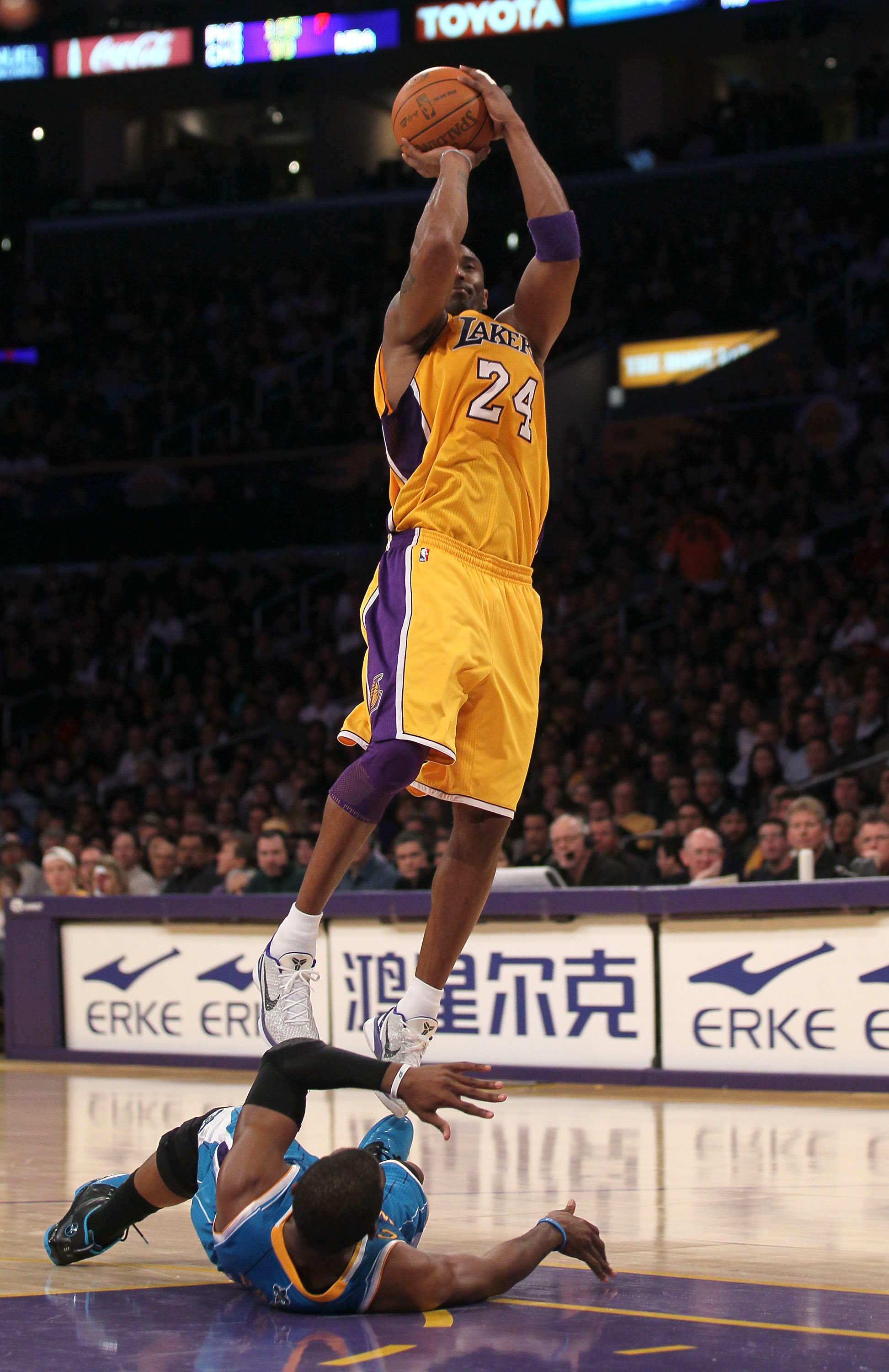 LOS ANGELES, CA - JANUARY 07:  Kobe Bryant #24 of the Los Angeles Lakers shoots over fallen Chris Paul #3 of the New Orleans Hornets at Staples Center on January 7, 2011 in Los Angeles, California.  The Lakers won 101-97.  NOTE TO USER: User expressly ack