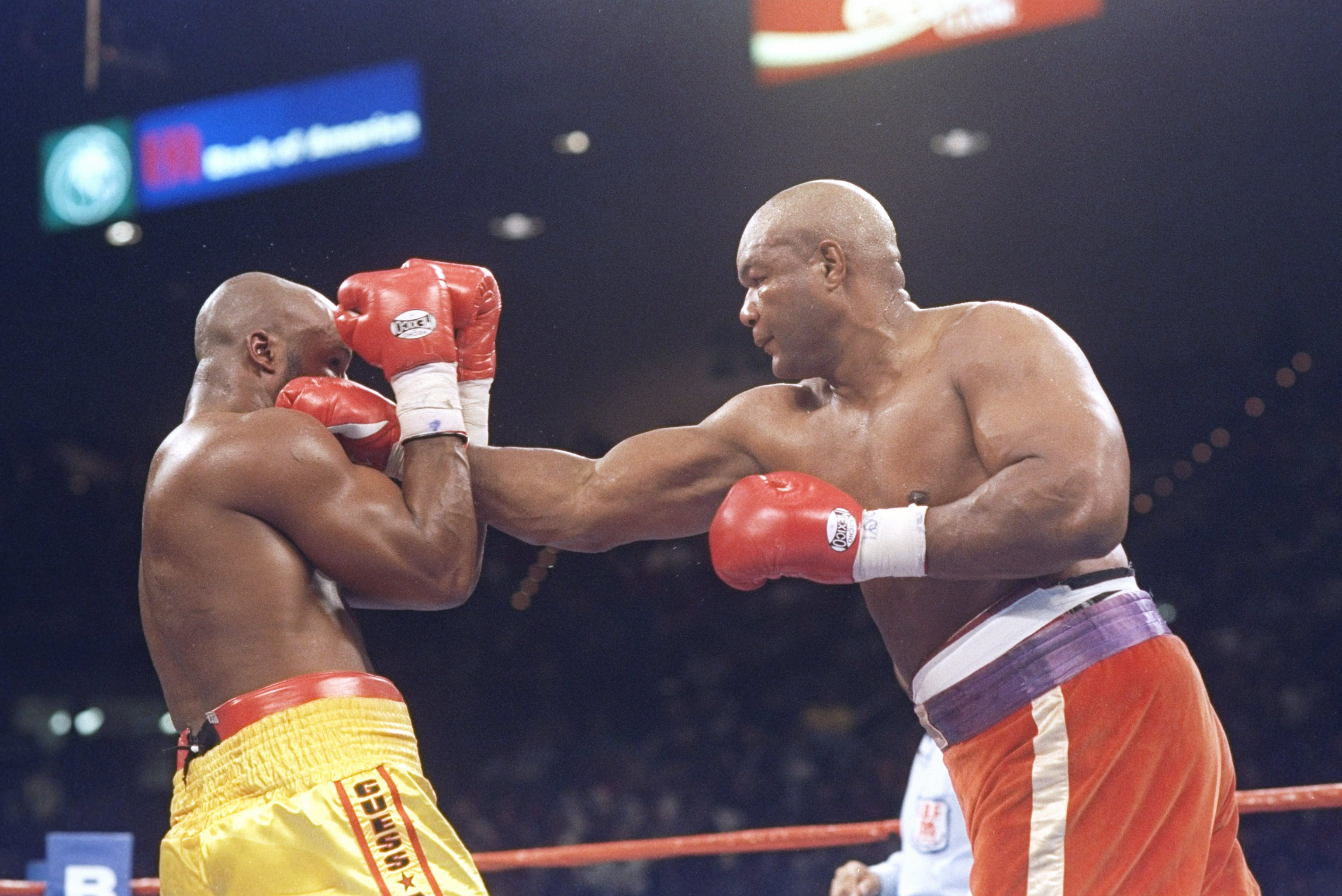 George Foreman (in the red trunks on the right) puts on a show against the 26-year-old world heavyweight champion Michael Mooer (in the yellow trunks) to win the heavyweight championship of the world at a record age of 45.
