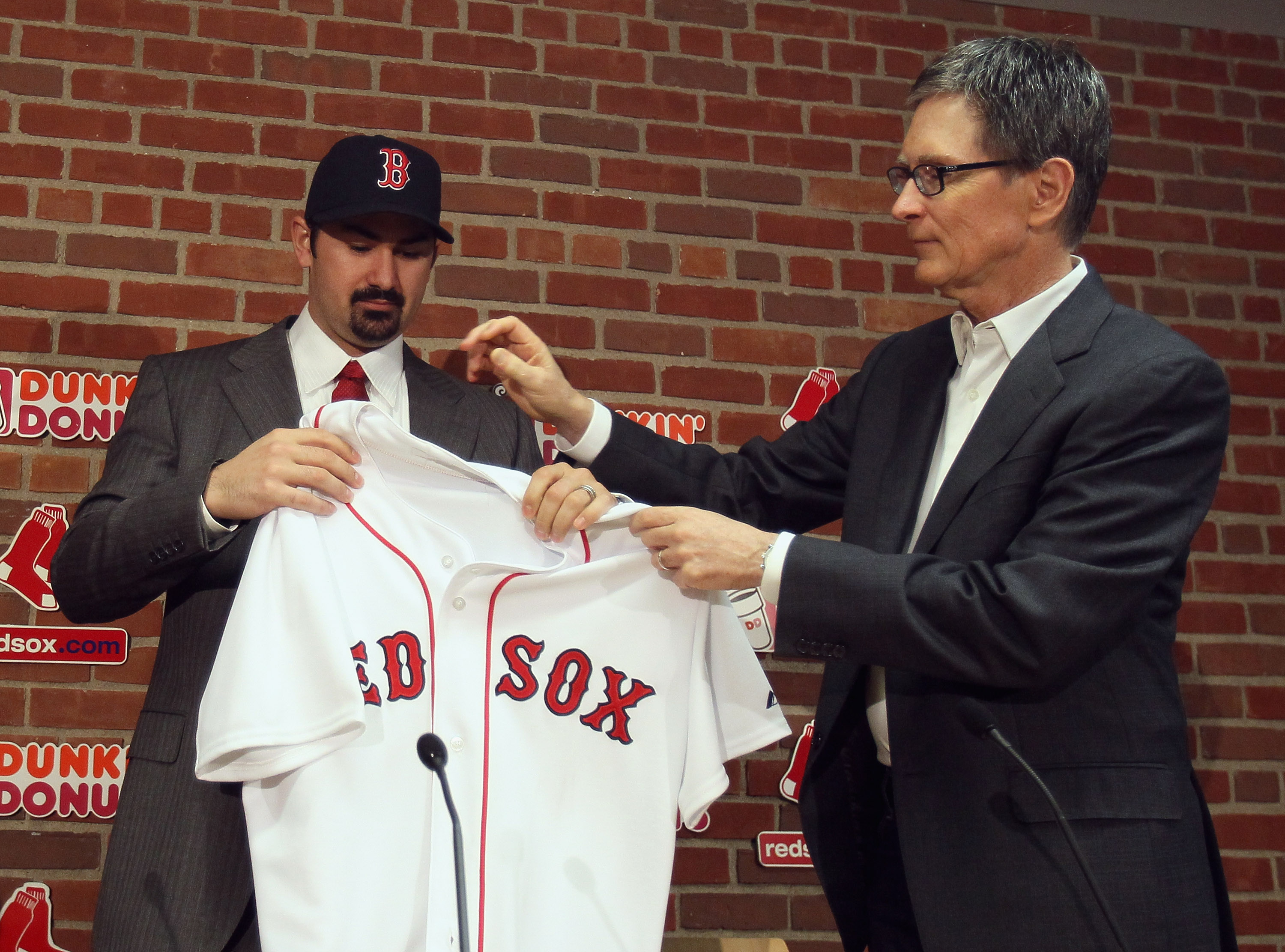 BOSTON, MA - DECEMBER 06:  Adrian Gonzalez (L) gets his jersey from principle owner John Henry during a press conference announcing that he signed with the Boston Red Sox on December 6,  2010 at Fenway Park in Boston, Massachusetts.  (Photo by Elsa/Getty