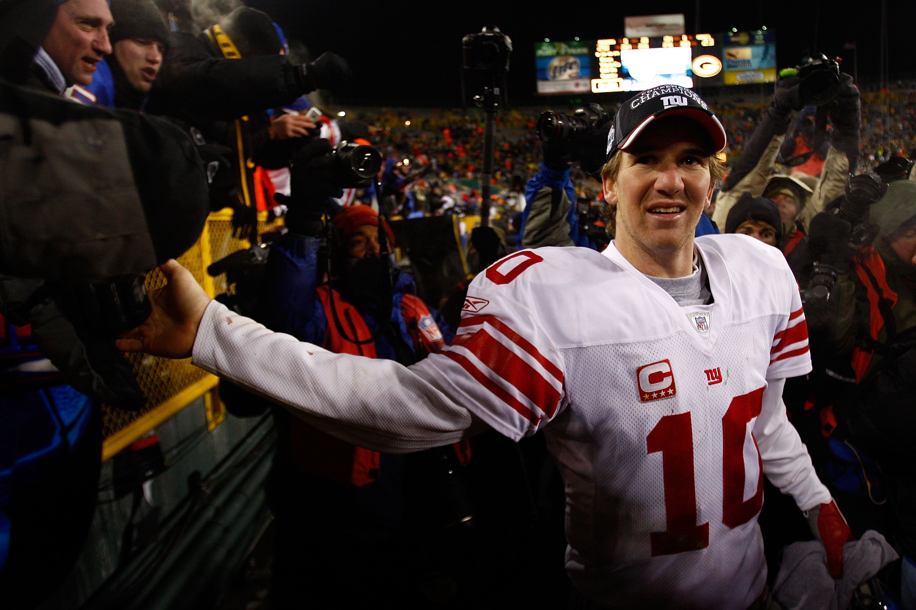 GREEN BAY, WI - JANUARY 20:  Quarterback Eli Manning #10 of the New York Giants celebrates with fans after winning the NFC championship game against the Green Bay Packers on January 20, 2008 at Lambeau Field in Green Bay, Wisconsin.   The Giants defeated