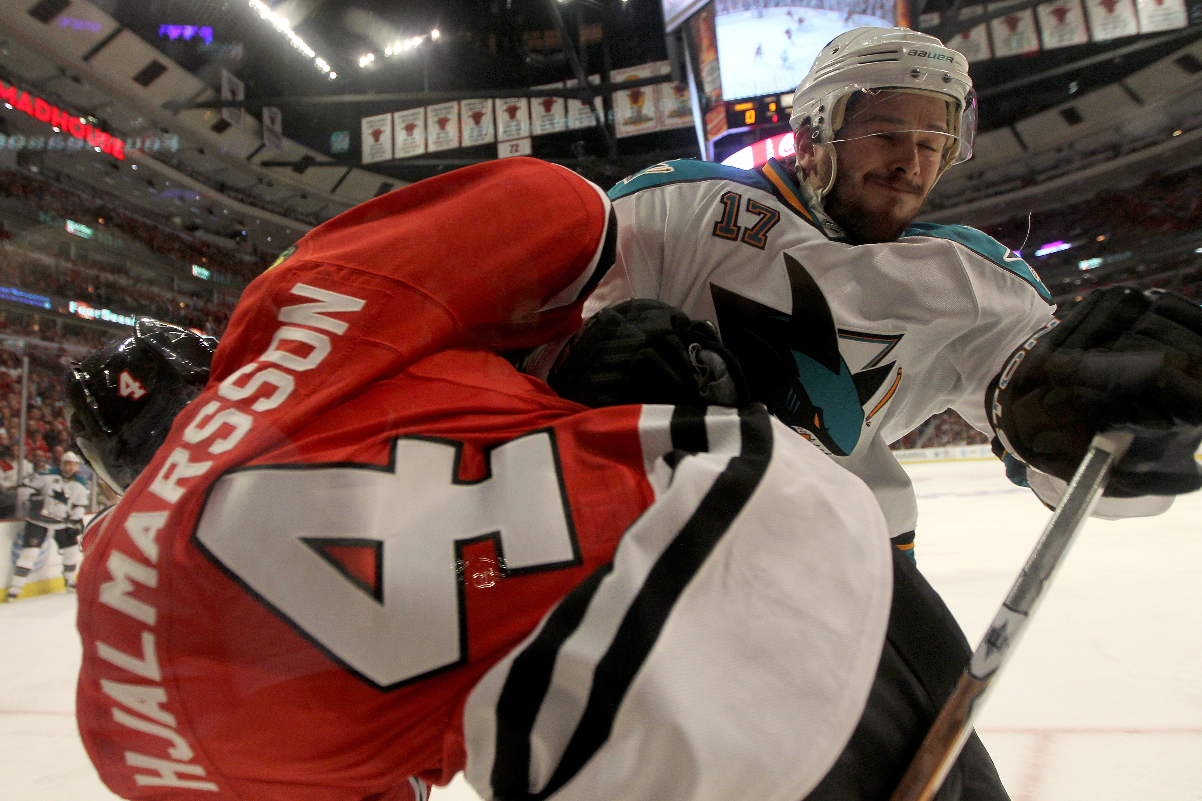CHICAGO - MAY 21:  Torrey Mitchell #17 of the San Jose Sharks checks Niklas Hjalmarsson #4 of the Chicago Blackhawks into the boards in the first period of Game Three of the Western Conference Finals during the 2010 NHL Stanley Cup Playoffs at the United