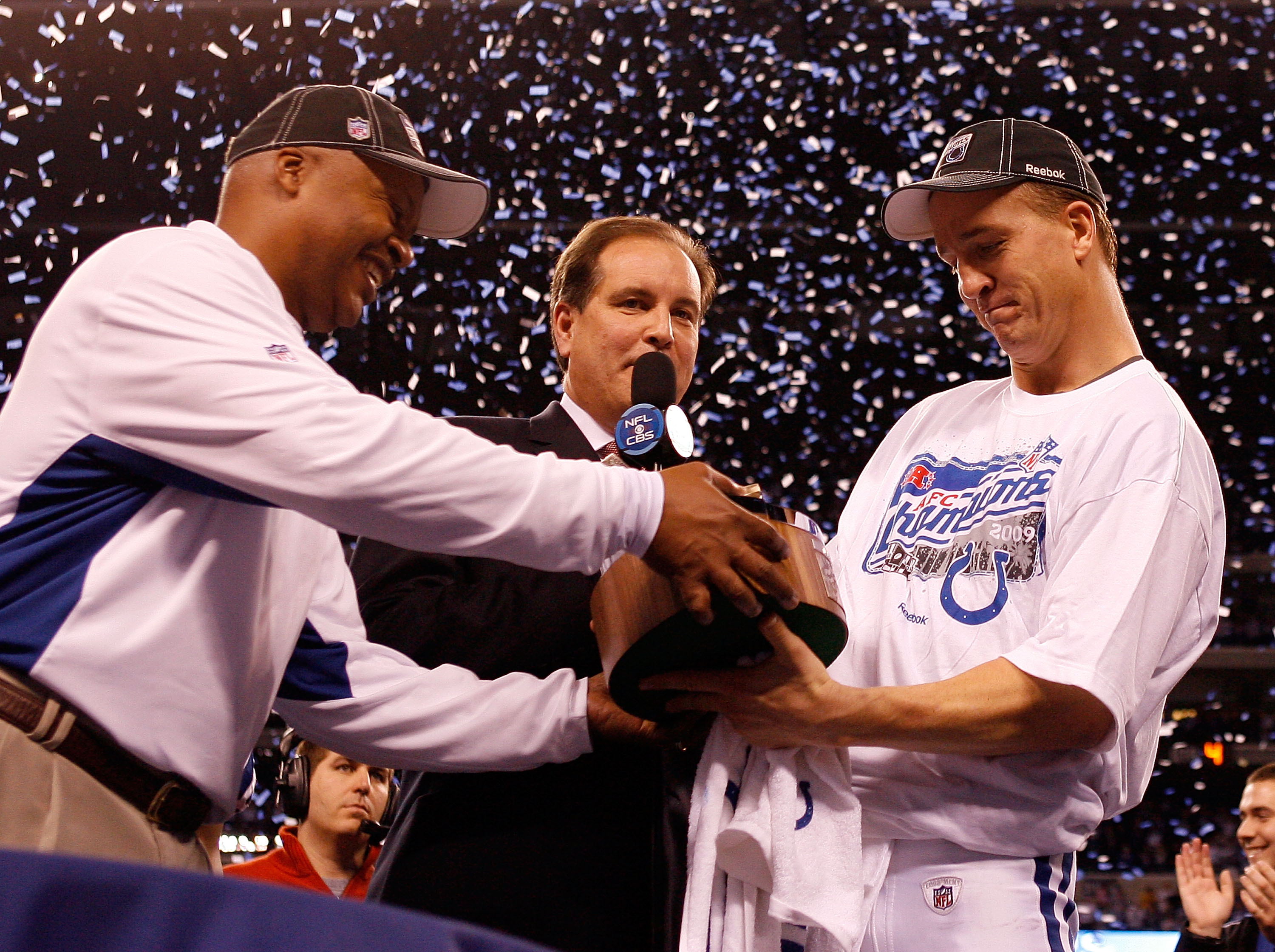 INDIANAPOLIS - JANUARY 24:  Head coach Jim Caldwell hands quarterback Peyton Manning #18 of the Indianapolis Colts the Lamar Hunt trophy after the Colts defeated the New York Jets 30-17 to win the AFC Championship Game at Lucas Oil Stadium on January 24,