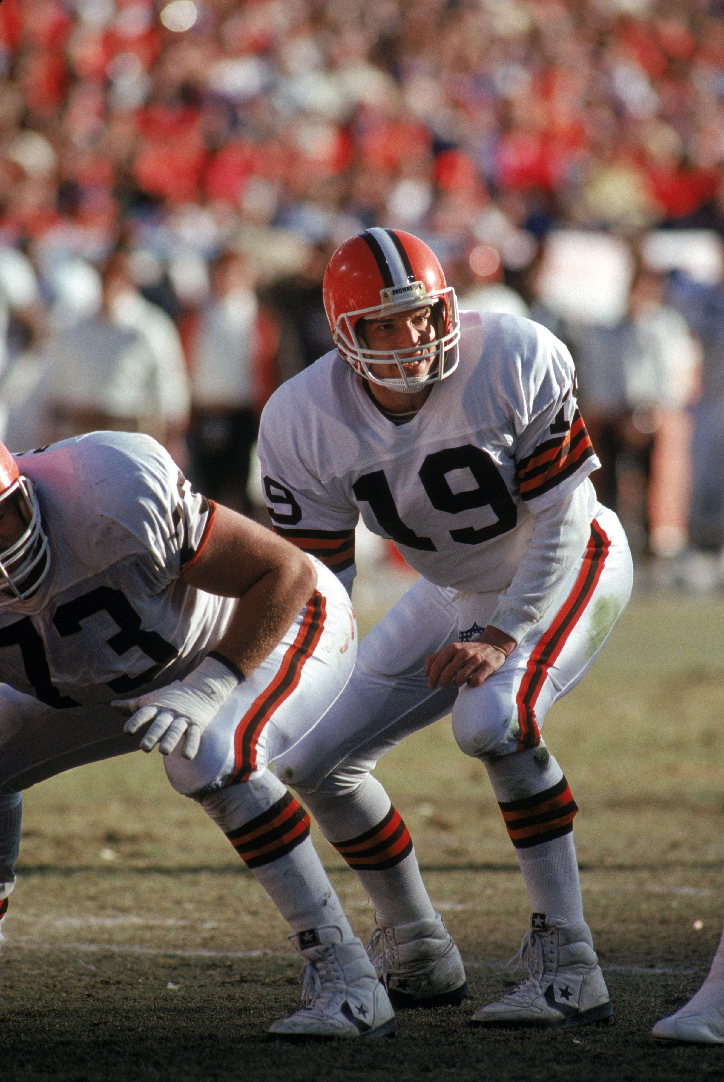 DENVER - JANUARY 17:  Quarterback Bernie Kosar #19 of the Cleveland Browns bends down for the snap during the 1987 AFC Championship game against the Denver Broncos at Mile High Stadium on January 17, 1988 in Denver, Colorado.  The Broncos won 38-33.  (Pho