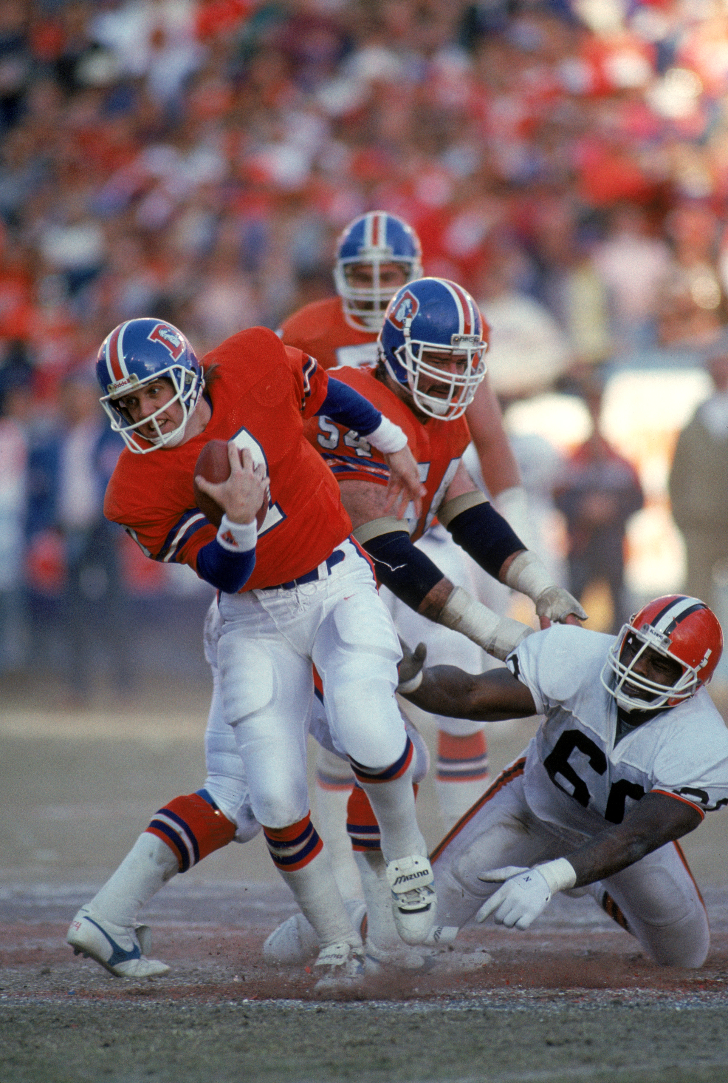 DENVER - JANUARY 17:  Quarterback John Elway #7 of the Denver Broncos breaks a tackle during the 1987 AFC Championship game against the Cleveland Browns at Mile High Stadium on January 17, 1988 in Denver, Colorado.  The Broncos won 38-33.  (Photo by Georg