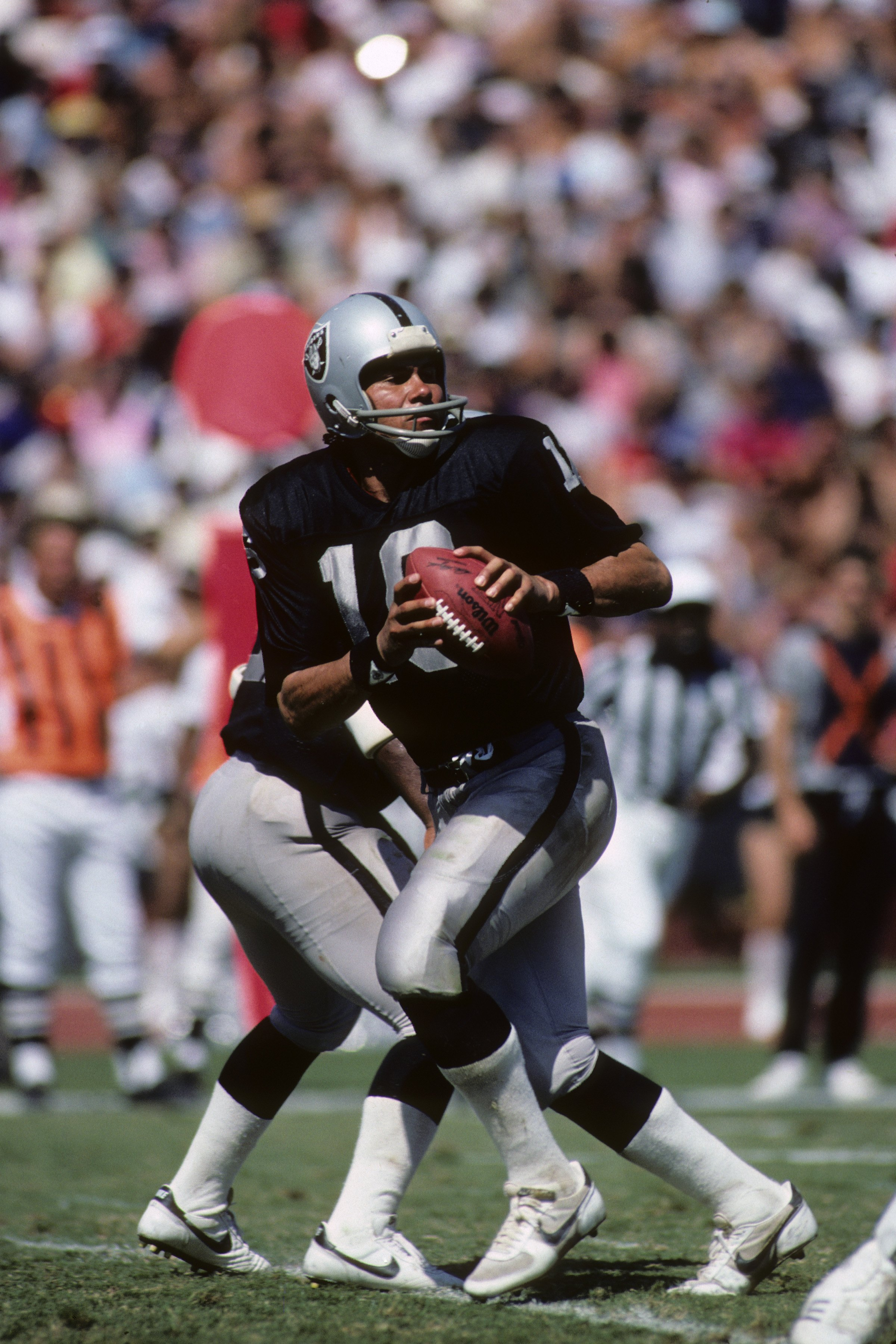 LOS ANGELES - SEPTEMBER 22:  Quarterback Jim Plunkett #16 of the Los Angeles Raiders drops back to pass during the game against the San Francisco 49ers at the Los Angeles Memorial Coliseum on September 22, 1985 in Los Angeles, California.  The 49ers won 3