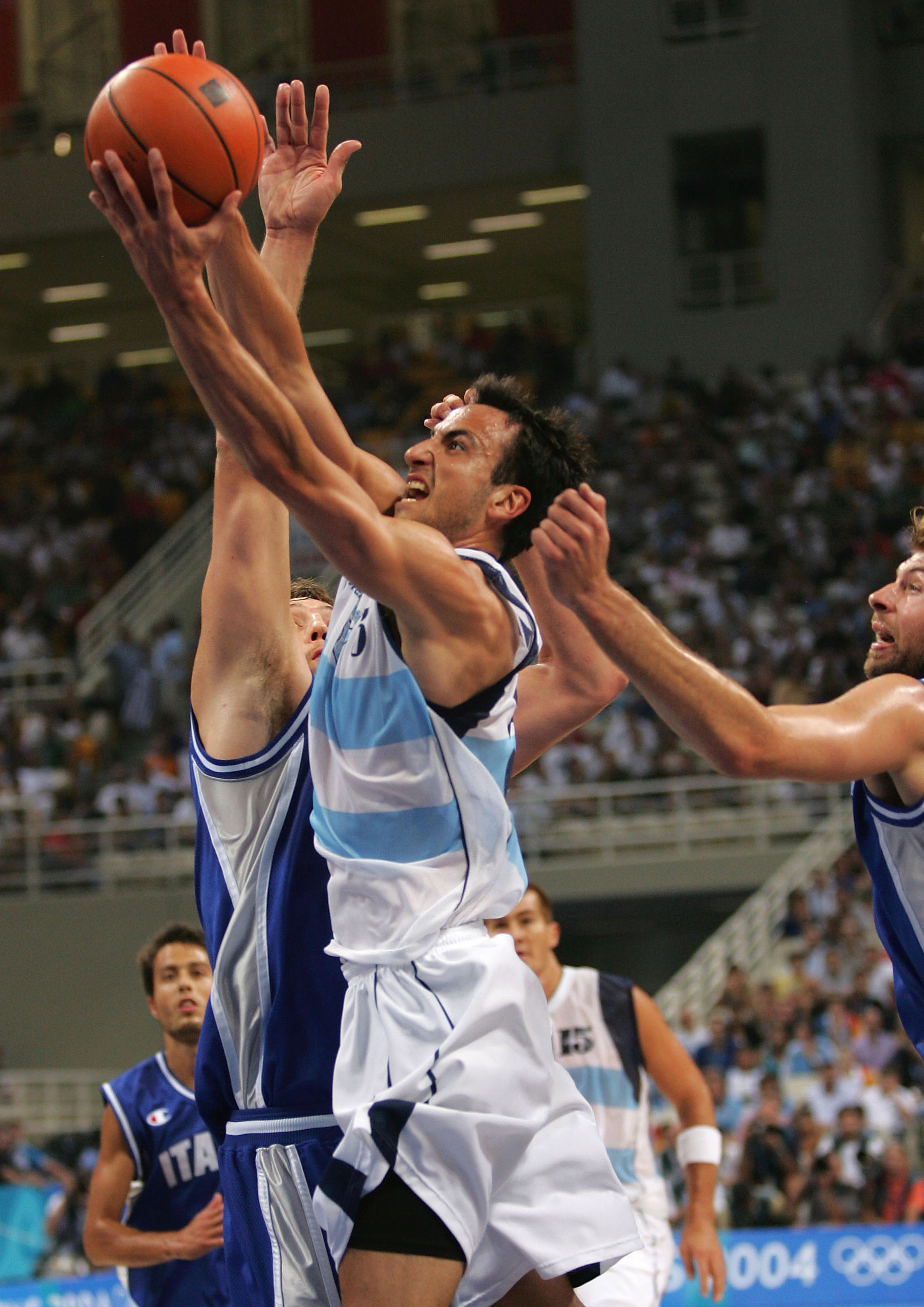 ATHENS - AUGUST 28:  Emanuel Ginobili #5 of Argentina shoots over the defense of Italy during the men's basketball gold medal contest game on August 28, 2004 during the Athens 2004 Summer Olympic Games at the Indoor Hall of the Olympic Sports Complex in A