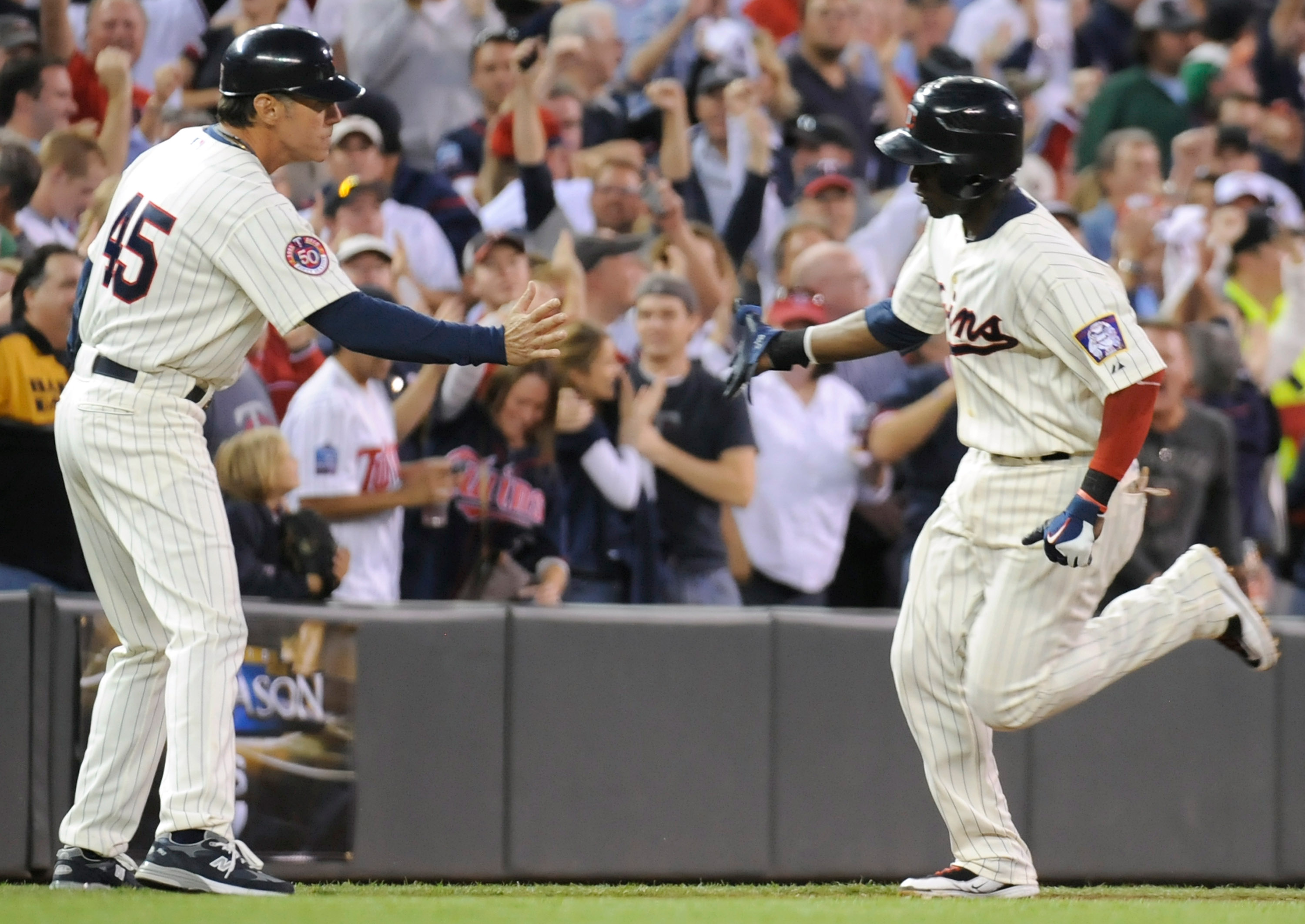 MINNEAPOLIS, MN - OCTOBER 7: Orlando Hudson #1 of the Minnesota Twins celebrates a solo home run with third base coach Scott Ullger #45 in the sixth inning during game two of the ALDS game against the Minnesota Twins on October 7, 2010 at Target Field in