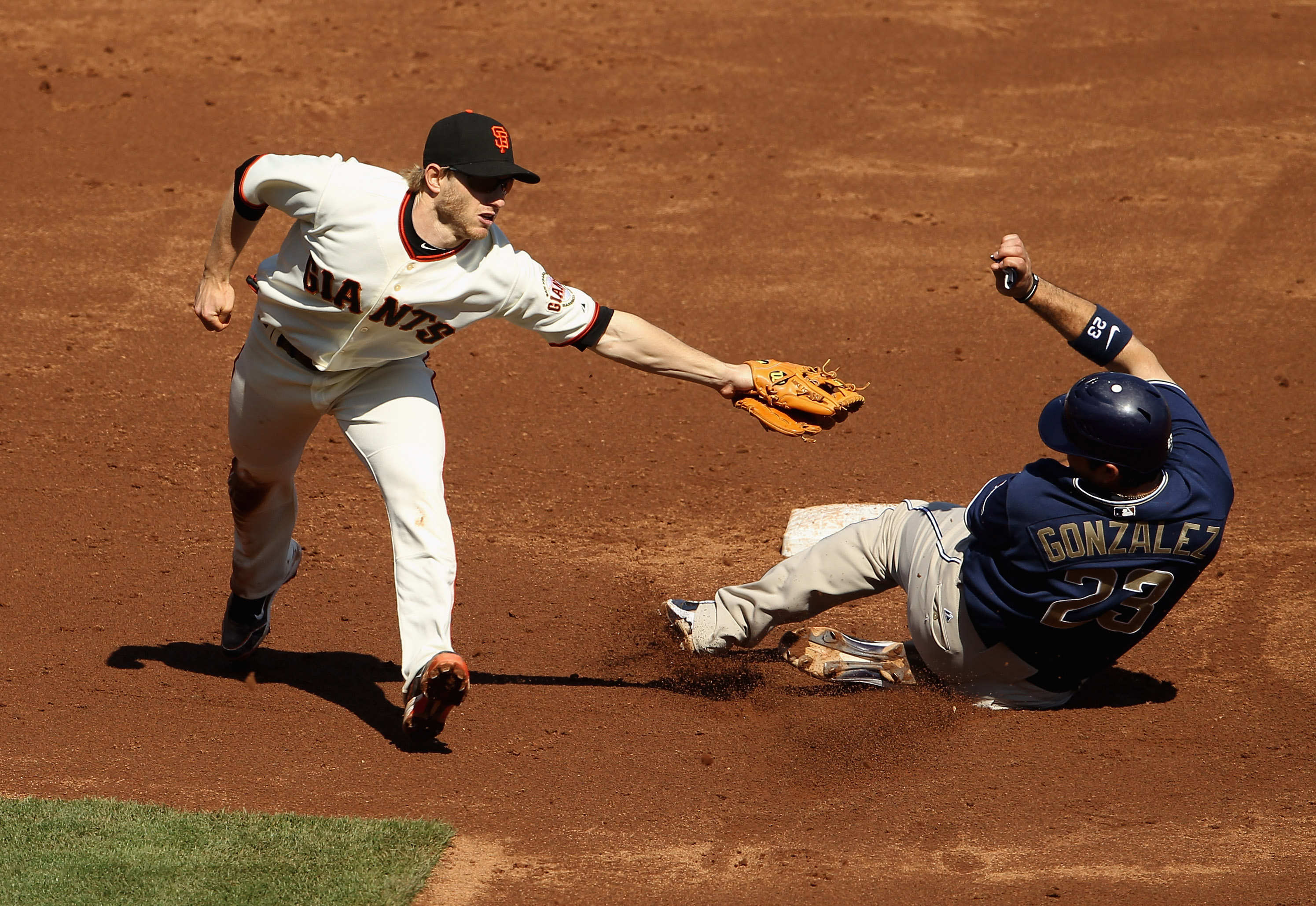 SAN FRANCISCO - OCTOBER 02:  Adrian Gonzalez #23 of the San Diego Padres slides to avoid the tag of Mike Fontenot #14 of the San Francisco Giants that was wide due to a throwing error by Pablo Sandoval at AT&T Park on October 2, 2010 in San Francisco, Cal
