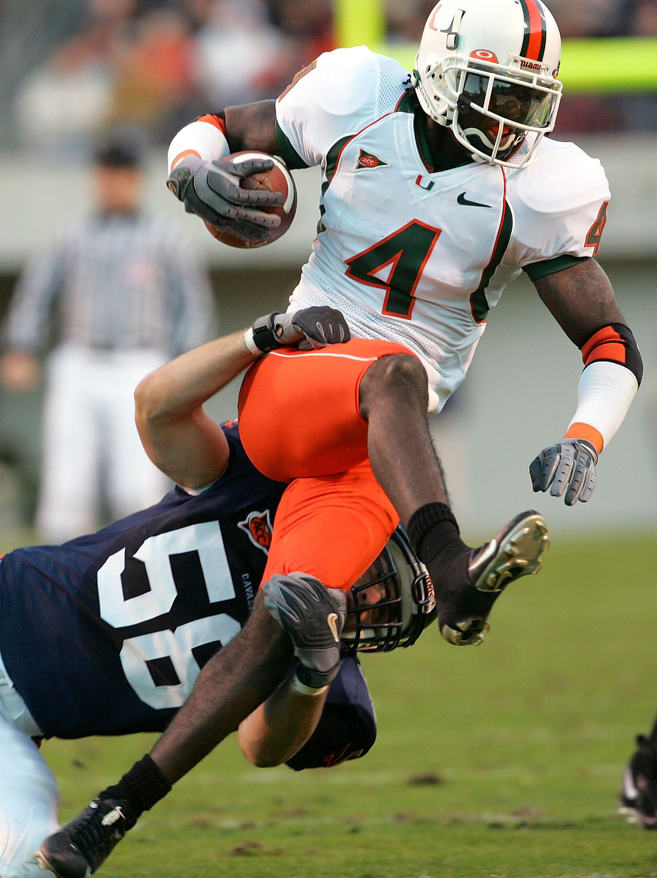 CHARLOTTESVILLE, VA - NOVEMBER 13:  Devin Hester #4 of the Miami Hurricanes carries the ball on a kickoff return as Jon Thompson #58 of the Virginia Cavaliers defends during the first half of the game on November 13, 2004 at David A. Harrison III Field at
