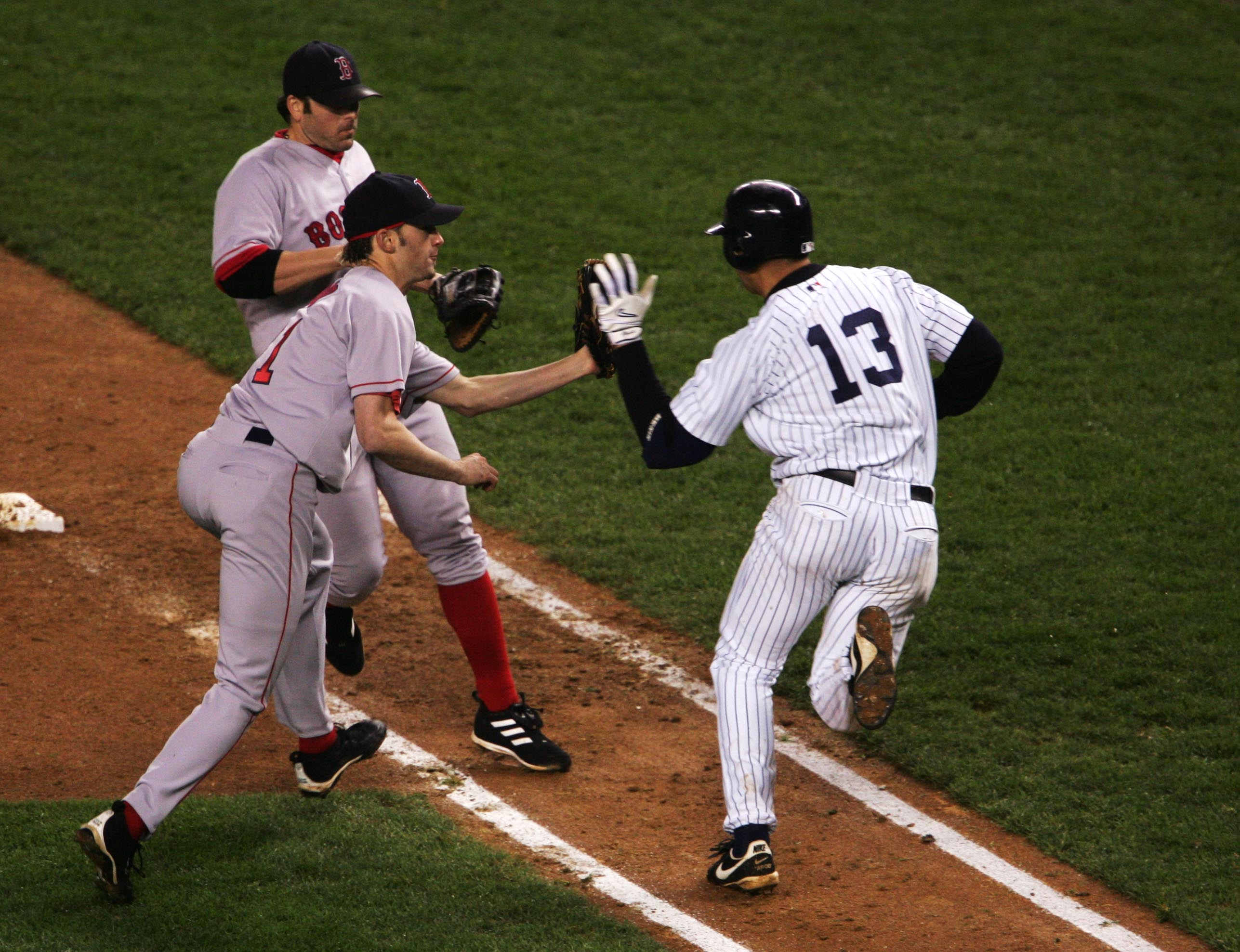 NEW YORK - OCTOBER 19:  Pitcher Bronson Arroyo #61 of the Boston Red Sox has the ball knocked out of his glove by batter Alex Rodriguez #13 of the New York Yankees on a tag-out at first base as first baseman Kevin Millar #15 looks on in the eighth inning