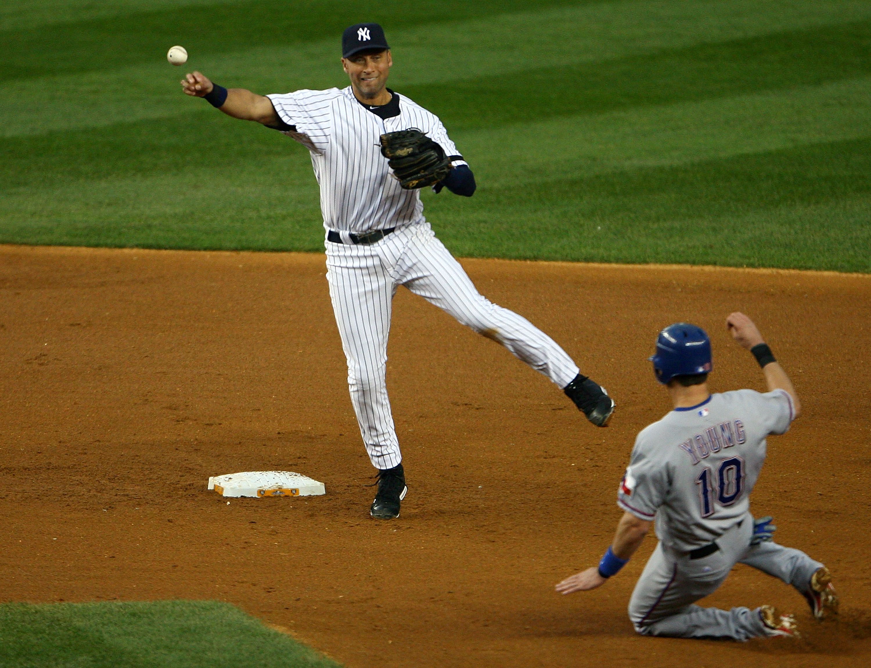 NEW YORK - OCTOBER 20:  Derek Jeter #2 of the New York Yankees turns a successful double play over a sliding Michael Young #10 of the Texas Rangers on a ball hit by Josh Hamilton #32 in the top of the fifth inning of Game Five of the ALCS during the 2010