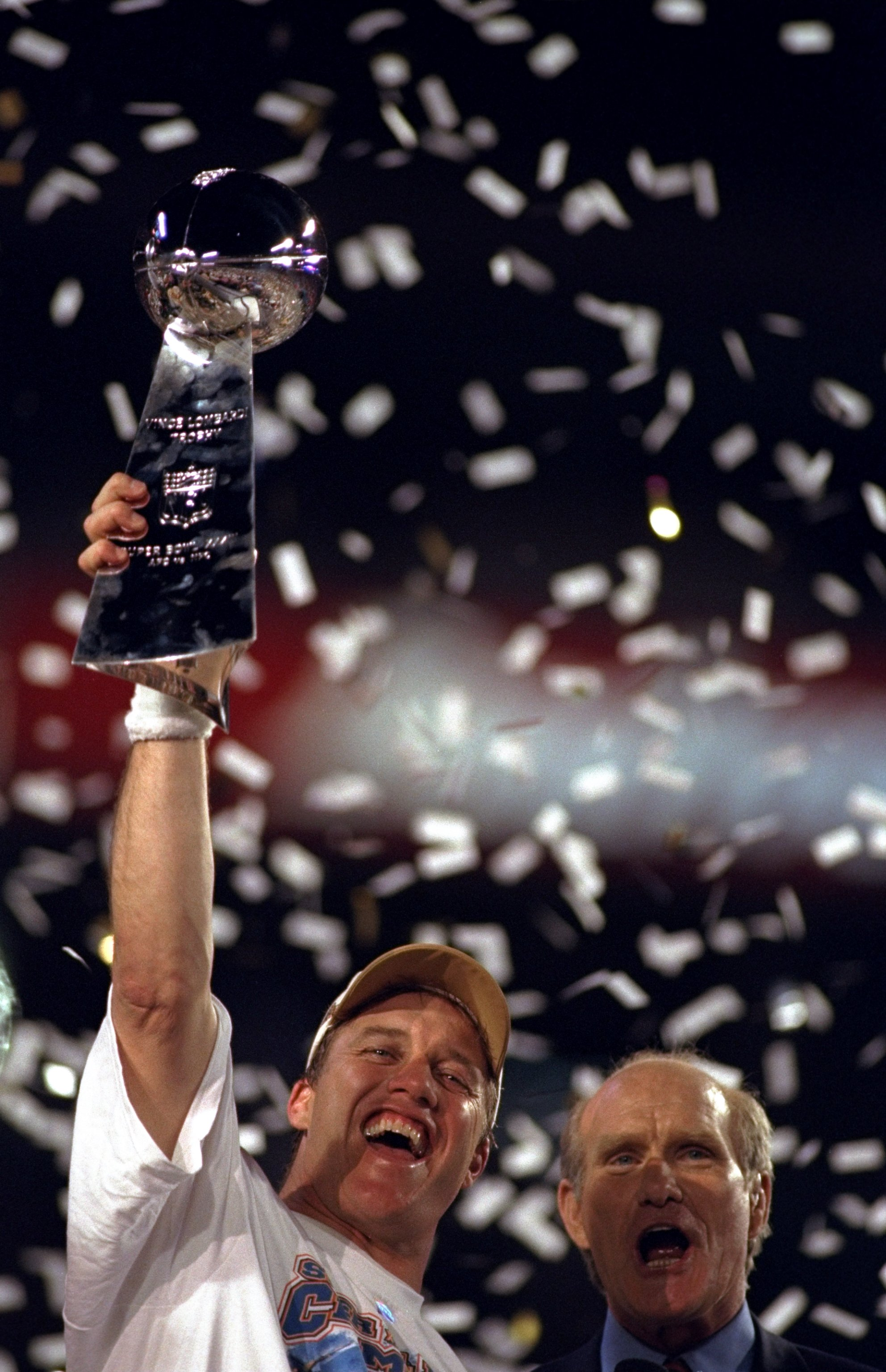 31 Jan 1999: Fox Sports TV analyst Terry Bradshaw cheers as confetti rains down on quarterback John Elway #7 of the Denver Broncos as he lifts the Vince Lombardi Trophy after defeating the Atlanta Falcons to win Super Bowl XXXIII at Pro Player Stadium in