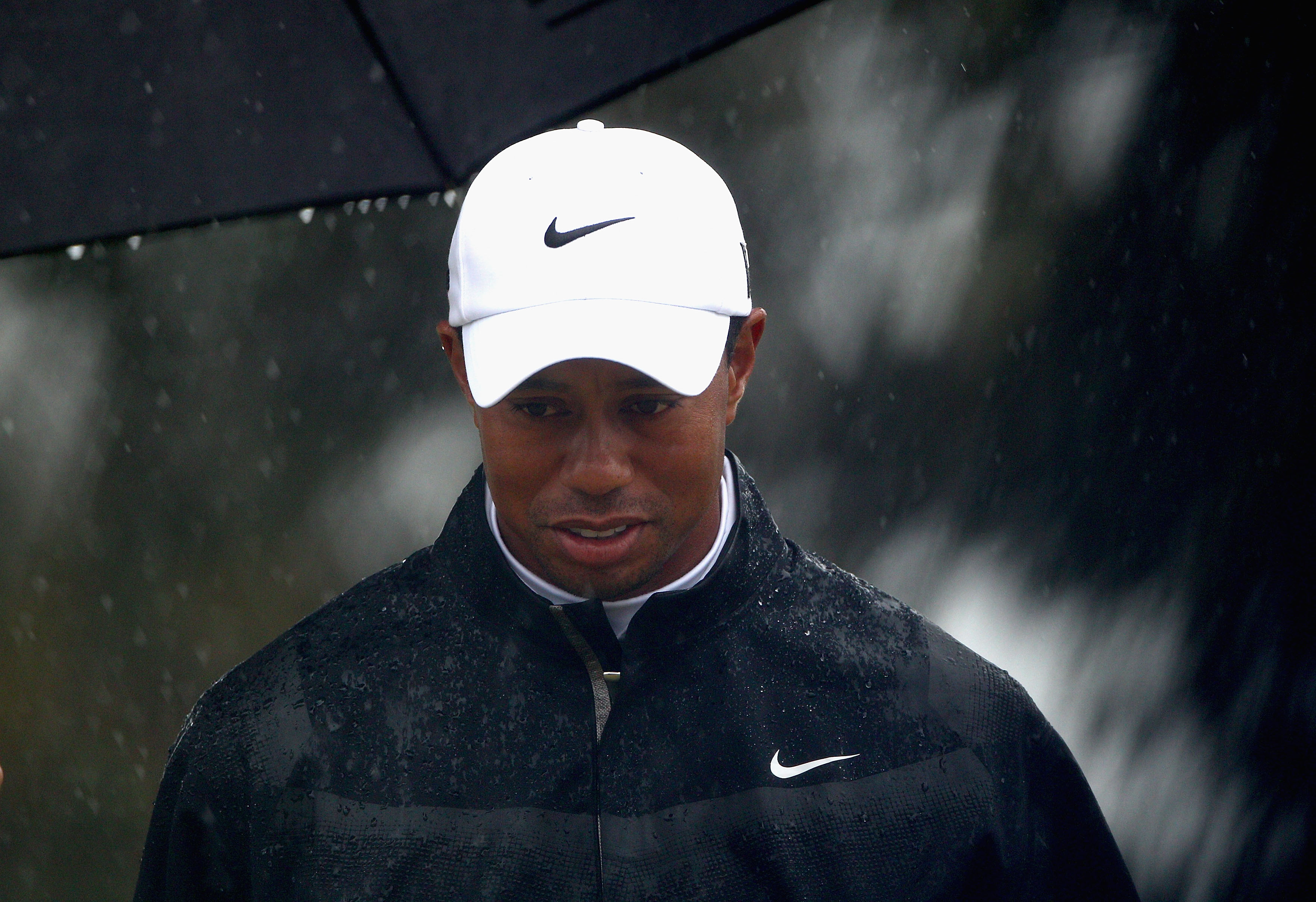MELBOURNE, AUSTRALIA - NOVEMBER 13:  Tiger Woods of the USA looks on as the rain falls during round three of the Australian Masters at The Victoria Golf Club on November 13, 2010 in Melbourne, Australia.  (Photo by Ryan Pierse/Getty Images)