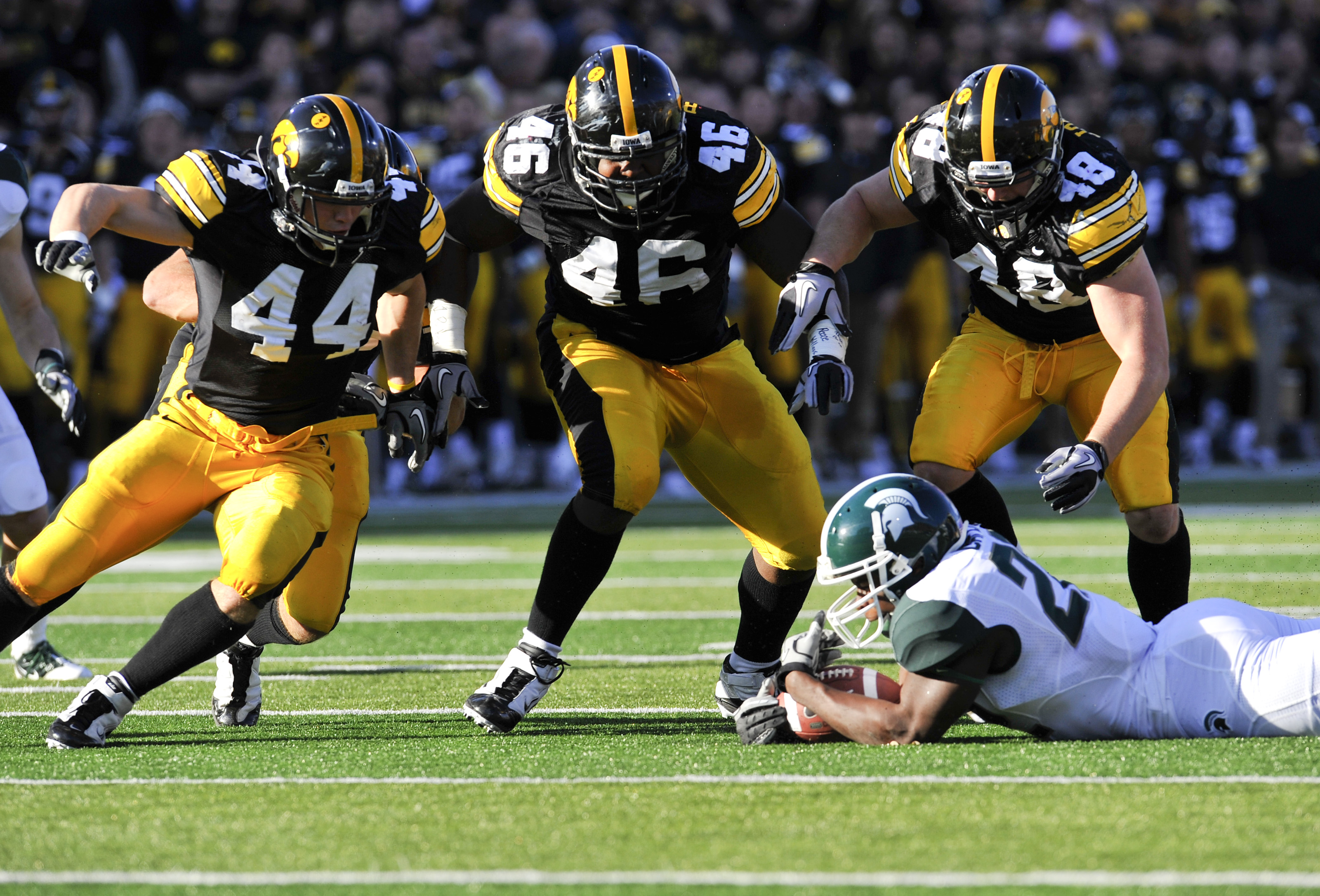 IOWA CITY, IA - OCTOBER 30: Running back Larry Caper #22 of the Michigan State Spartans recovers his fumble as line backer James Morris #44, defensive line man Christian Ballard #46, and line backer Troy Johnson #48 of the University of Iowa Hawkeyes clos