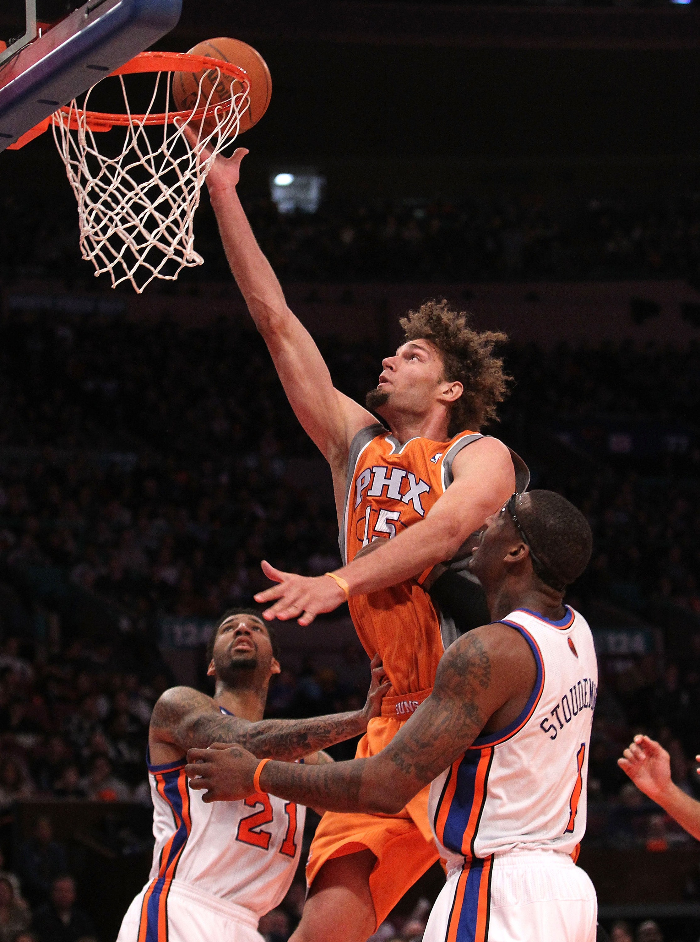 NEW YORK, NY - JANUARY 17: Robin Lopez #15 of the Phoenix Suns shoots the ball over Wilson Chandler #21 and Amar'e Stoudemire #1 of the New York Knicks at Madison Square Garden on January 17, 2011 in New York City. NOTE TO USER: User expressly acknowledge