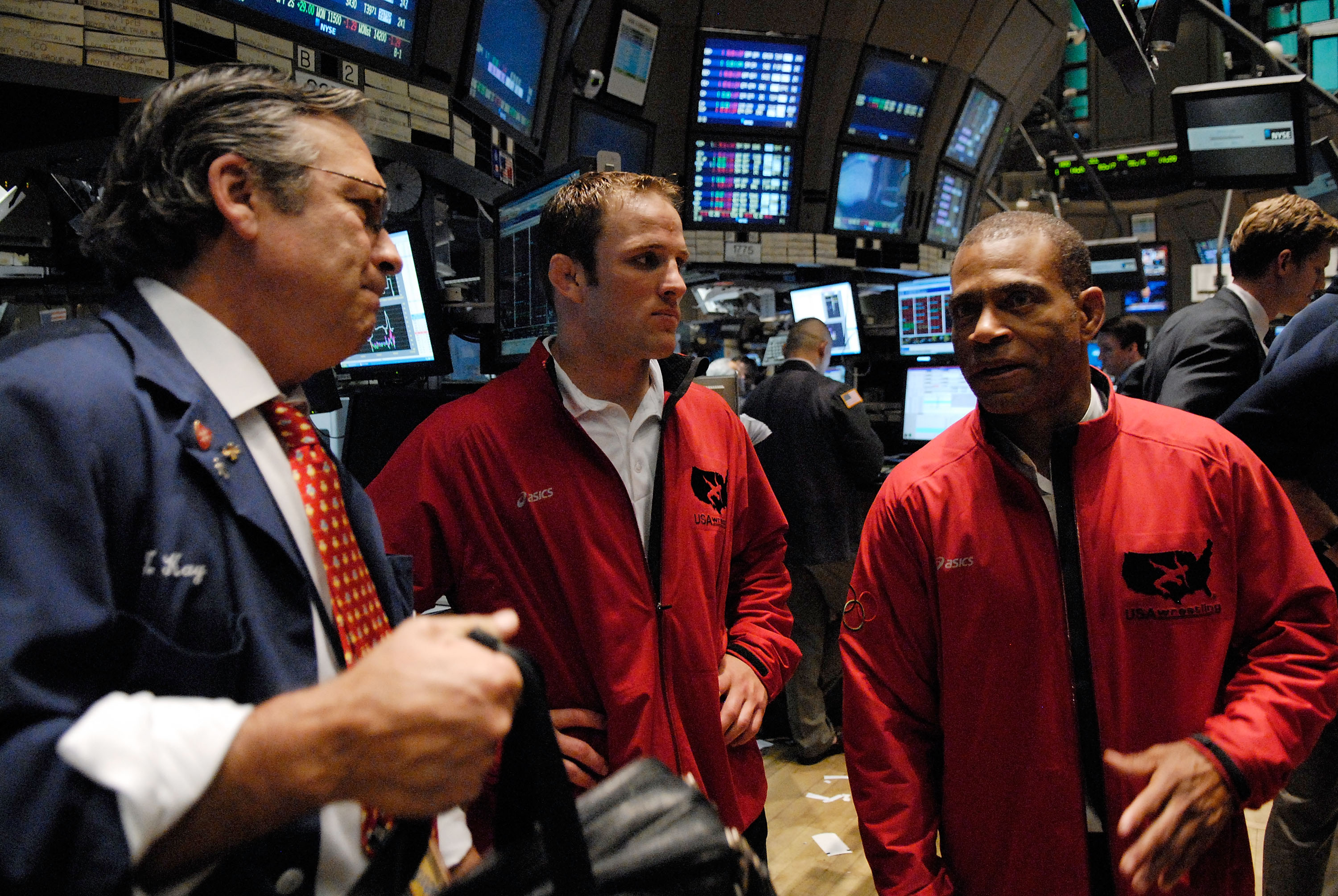NEW YORK - JUNE 20: U.S. National Wrestling Team member Brad Vering (C) and freestyle coach Lee Kemp (R) talk to a trader on the floor of the New York Stock Exchange June 20, 2008 in New York City. (Photo by Jonathan Fickies/Getty Images)